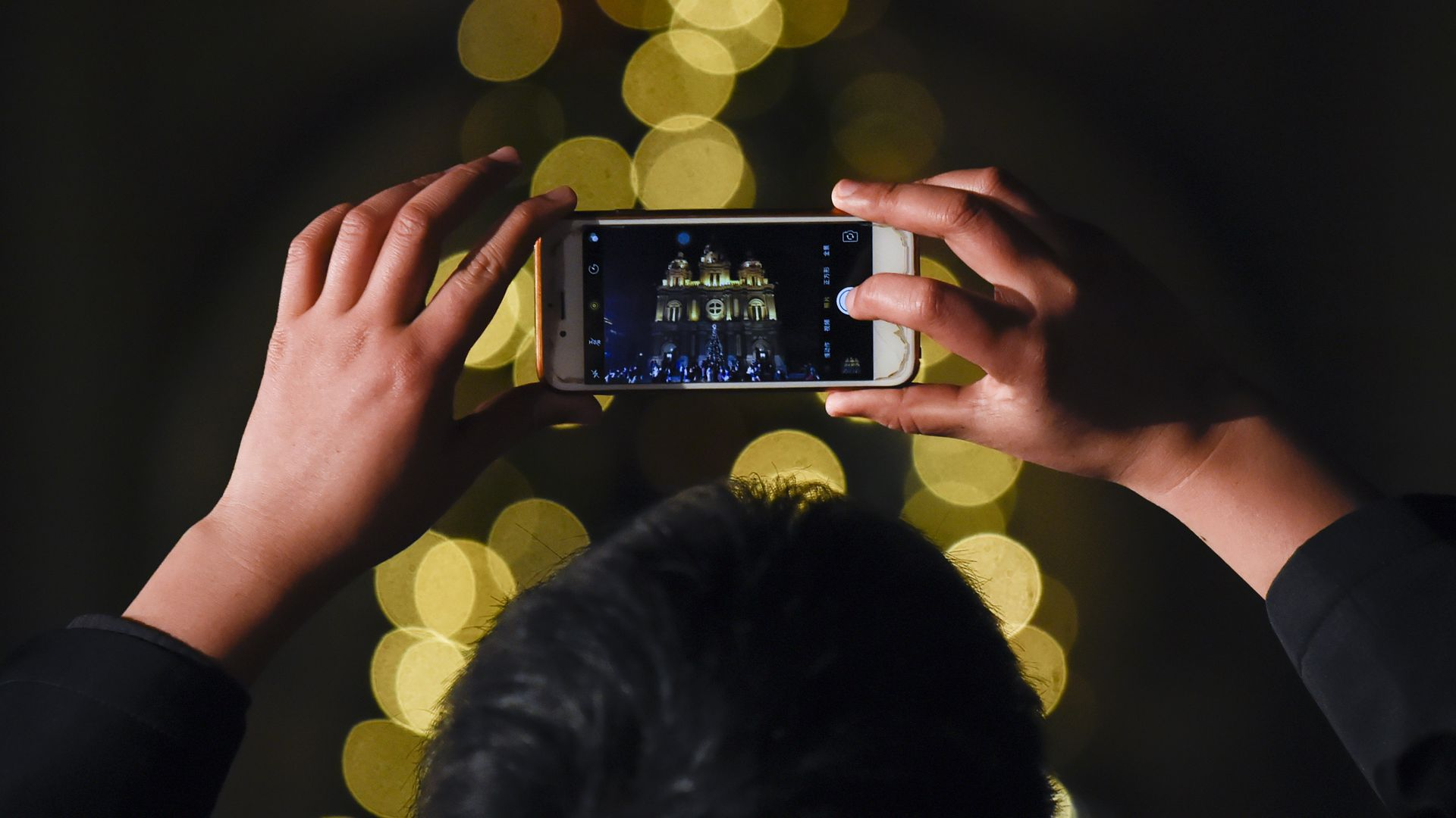 Man uses cell phone to take picture of Christmas lights, which are out of focus