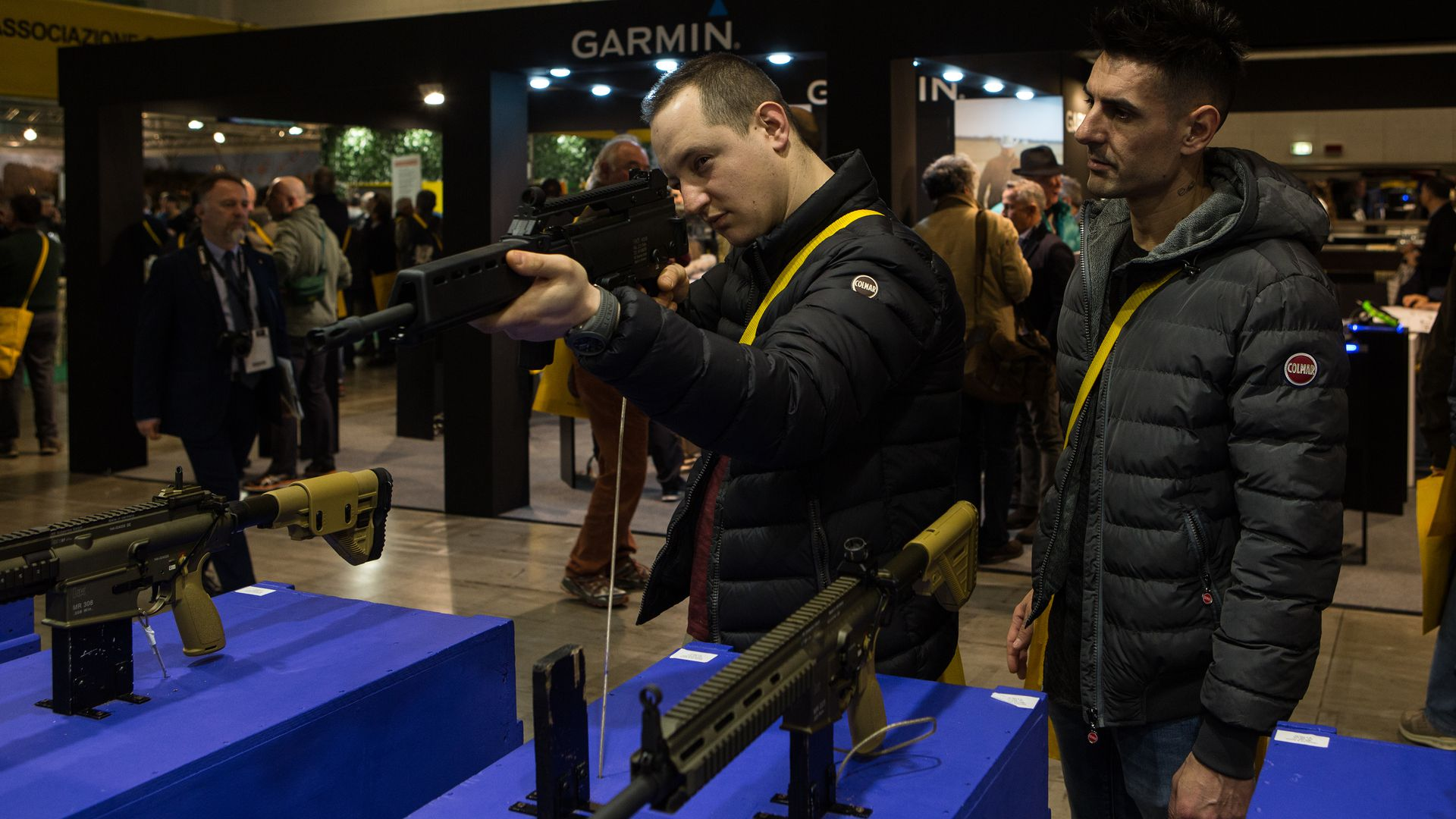two men trying out a gun at a gun show