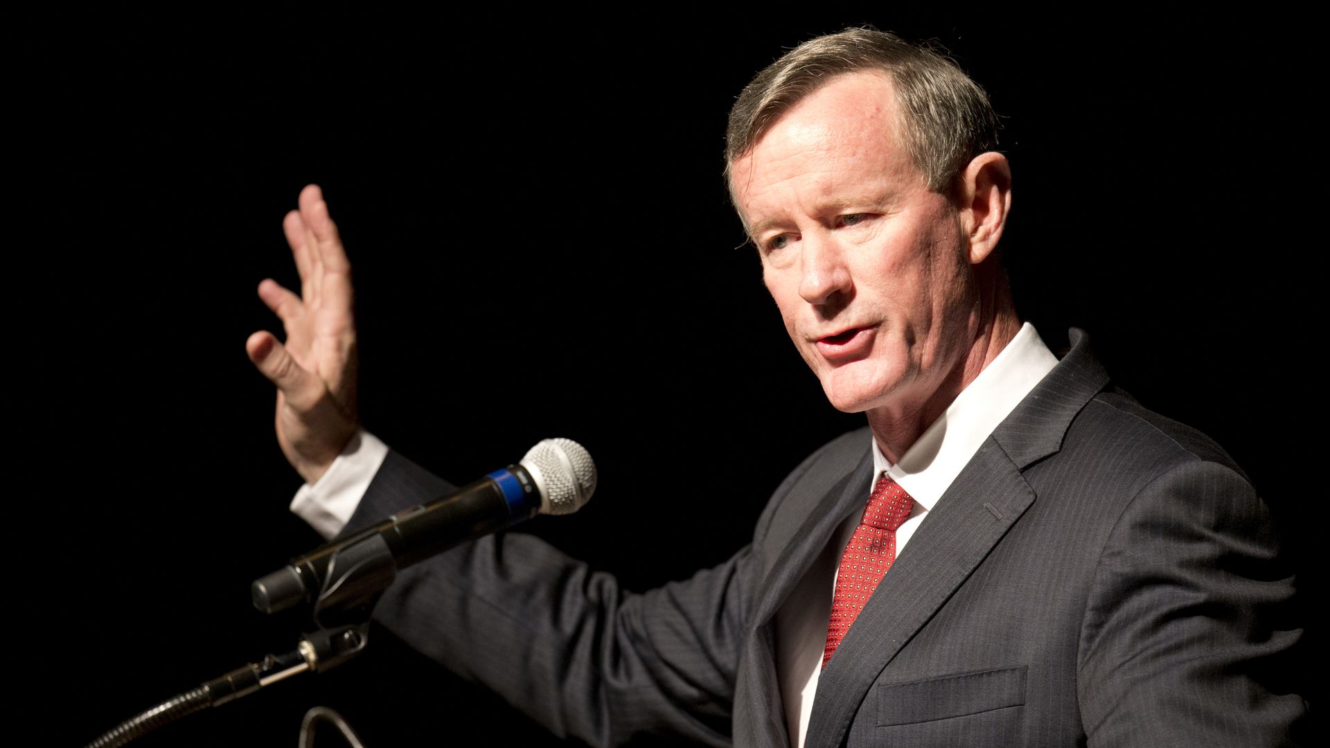 McRaven speaks at podium waving one hand.