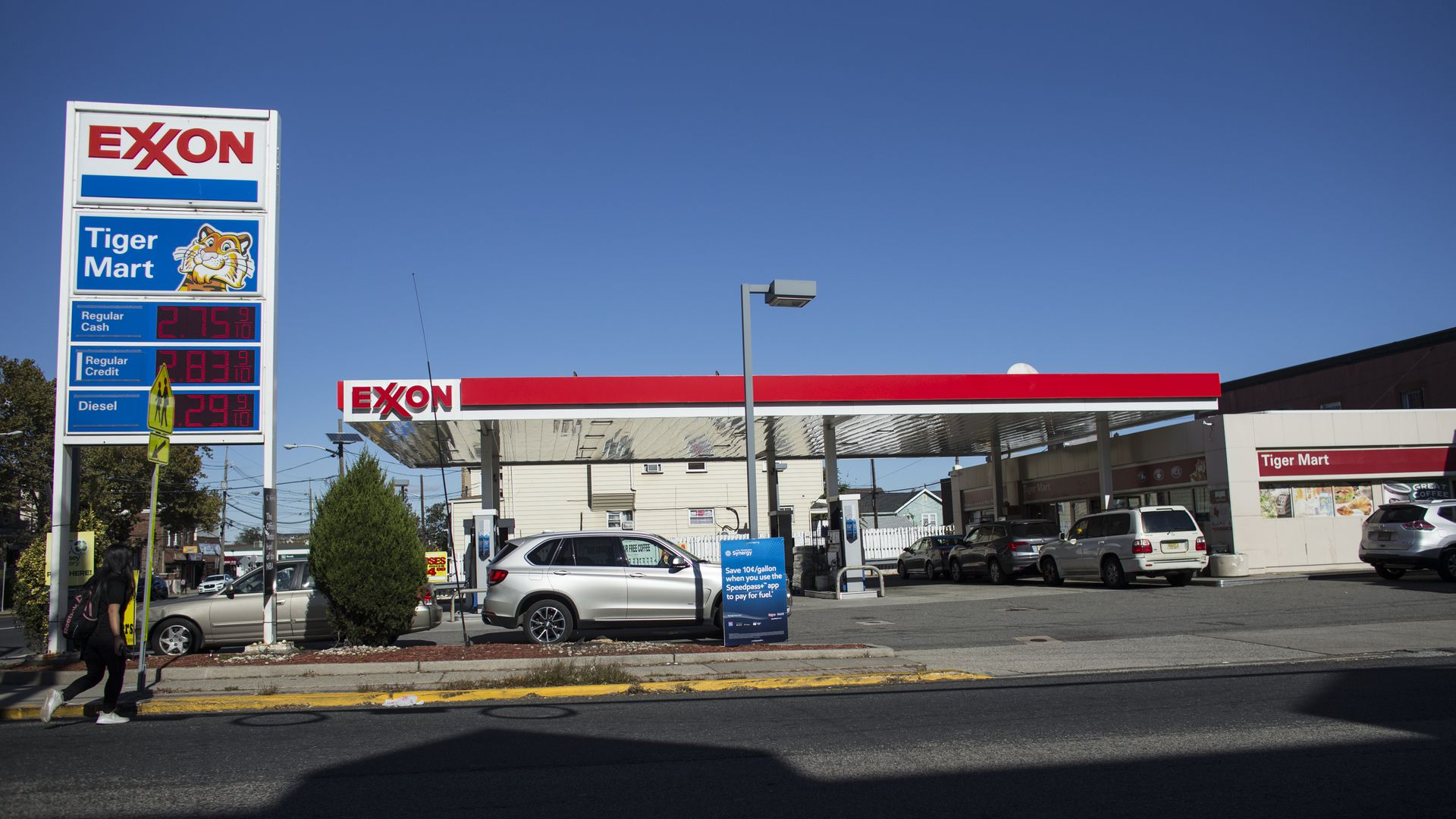 In this image, an ExxonMobil gas station is pictured behind an empty street.