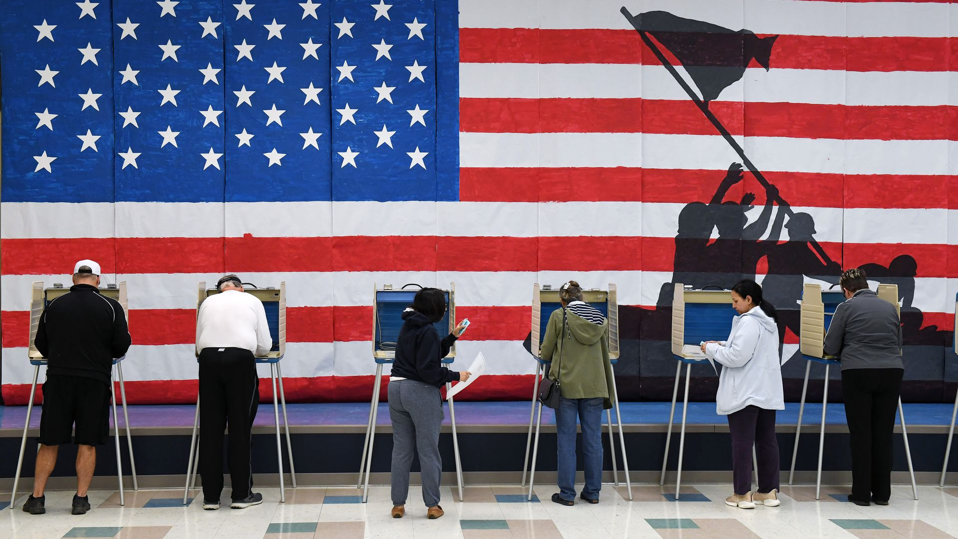 People voting at booths with an American flag background.