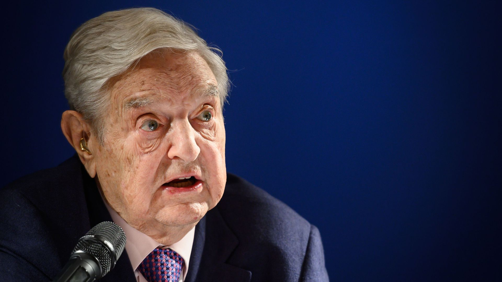 US investor and philanthropist George Soros speaks into a microphone.