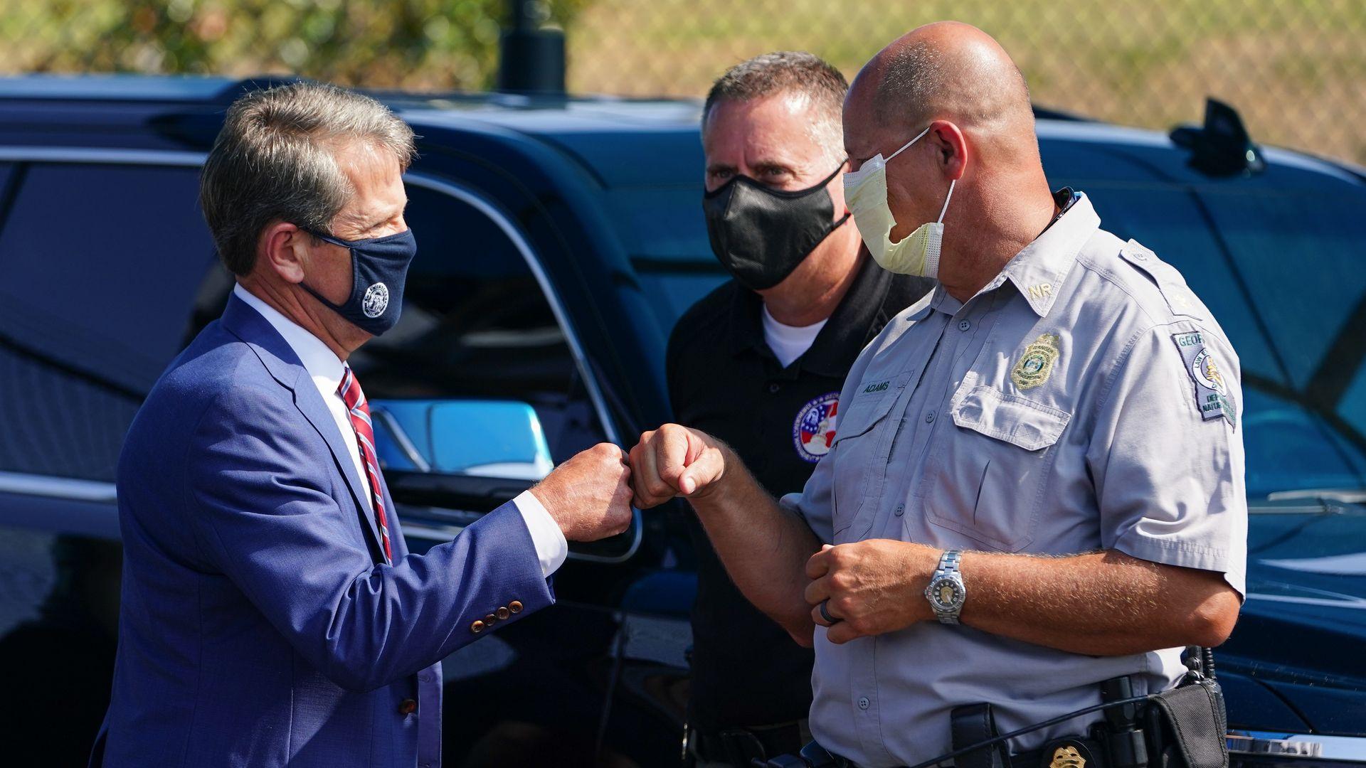 Gov. Brian Kemp of Georgia fist bumps a police officer.