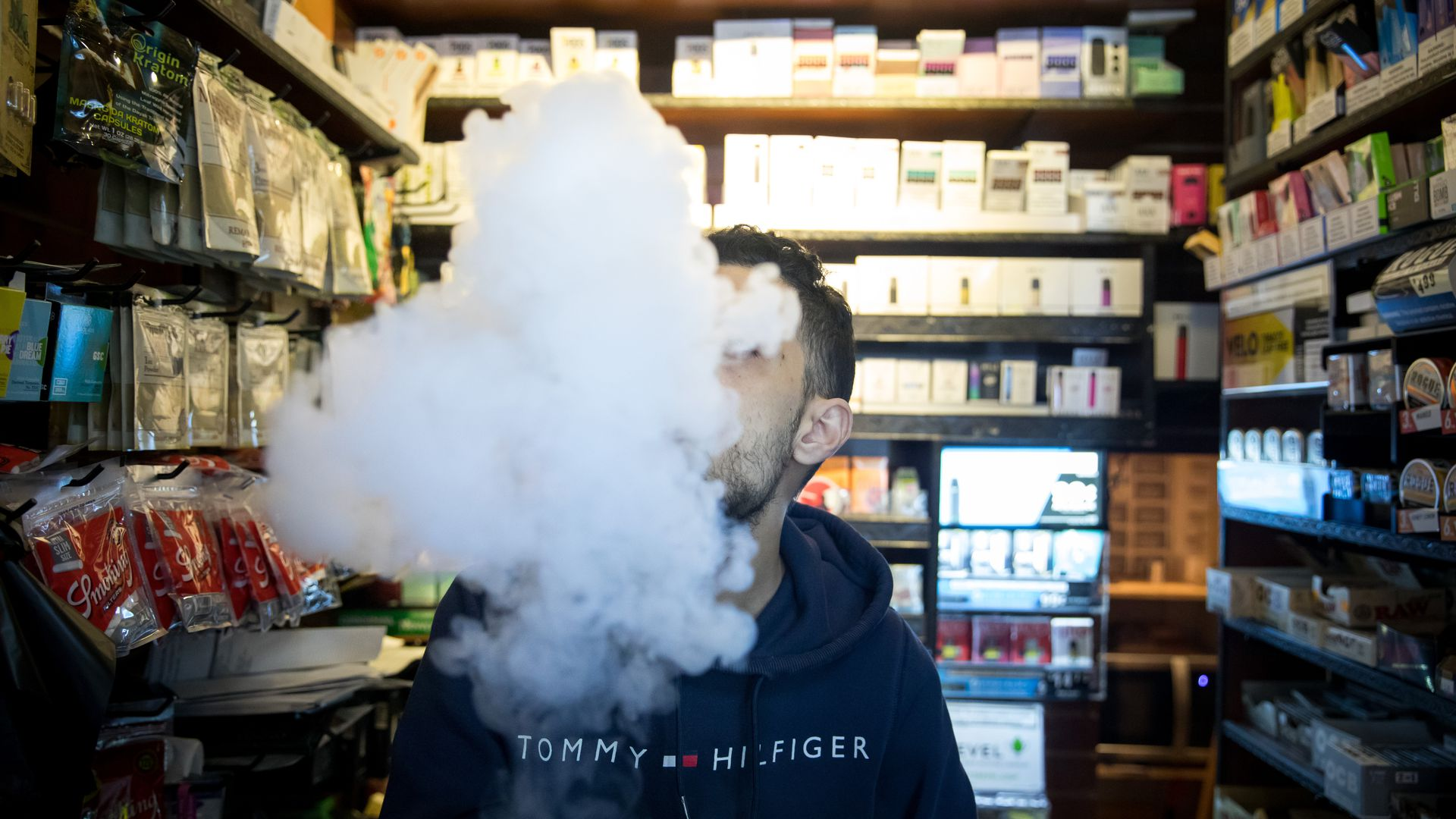 A photo of a person exhaling vapor while using an electronic cigarette device at a smoke shop