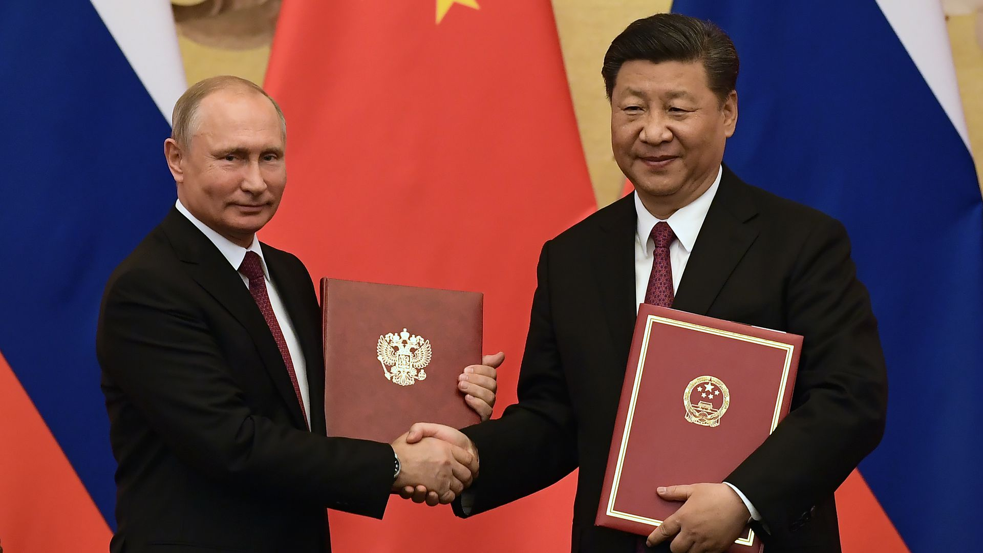 Chinese President Jinping congratulates Russian President Putin after presenting him with the Friendship Medal