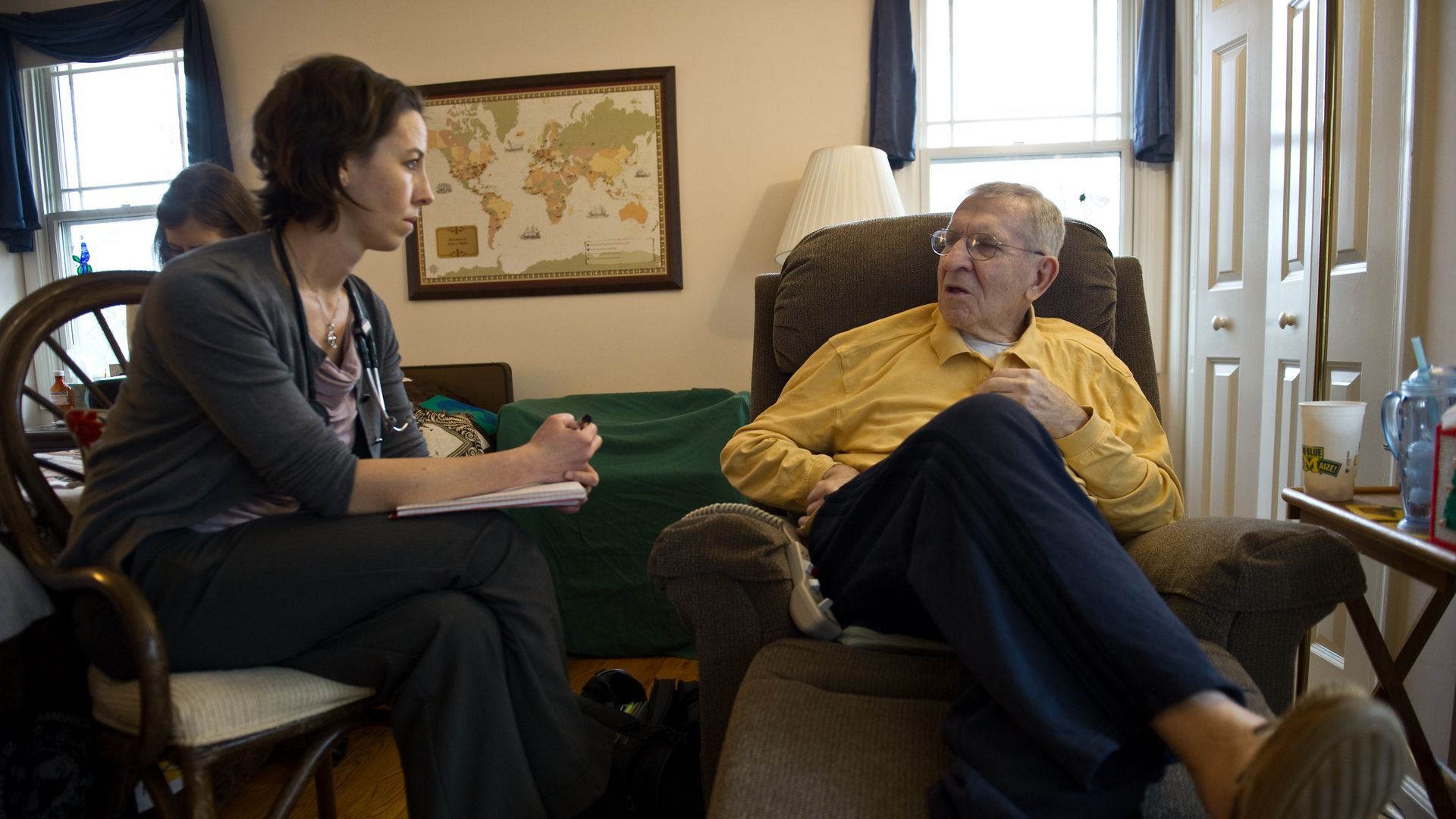 A neurologist meets with an elderly patient in his home.