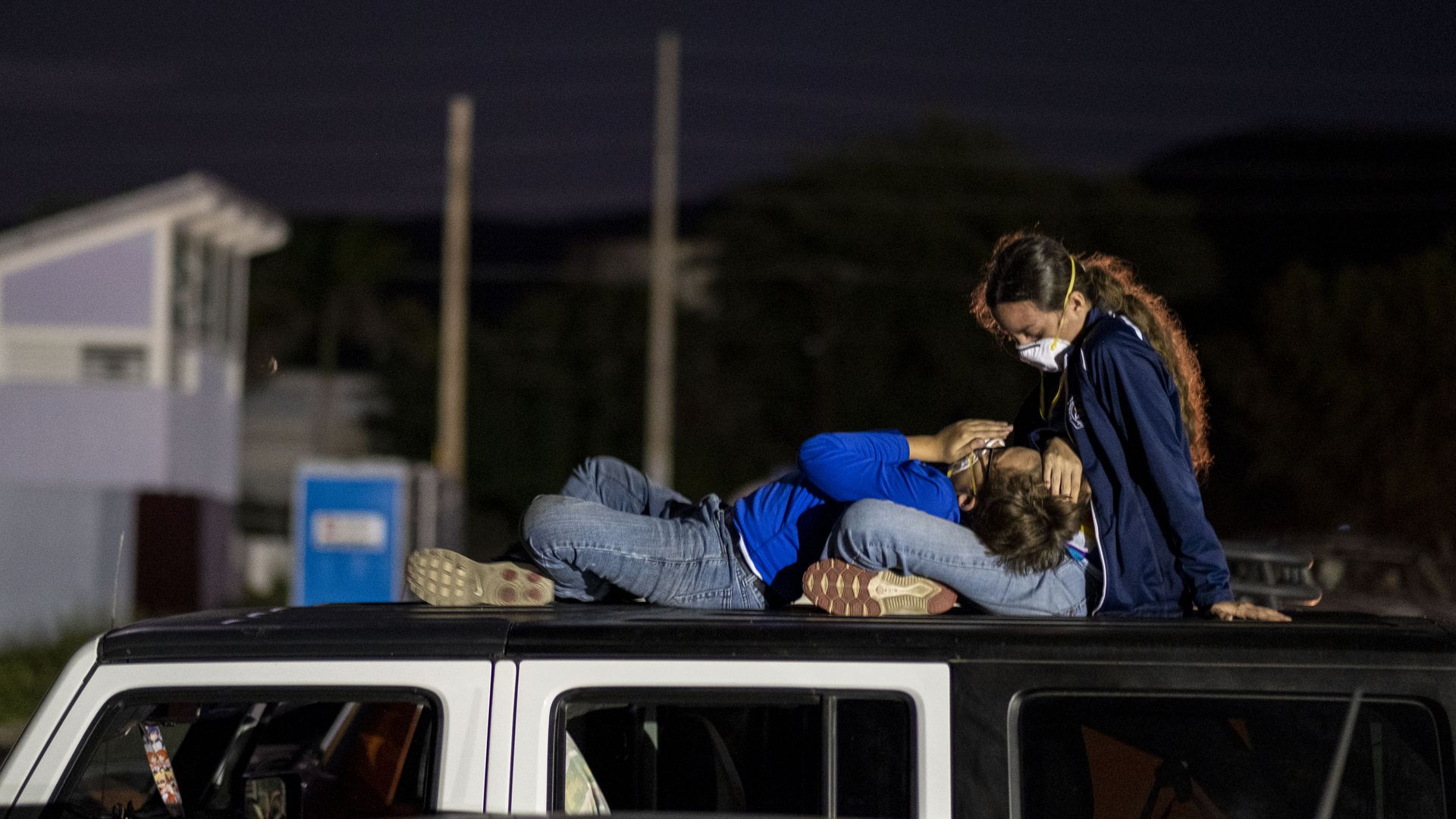 In this image, a child rests their head in a woman's lap on top of a car in Puerto Rico.