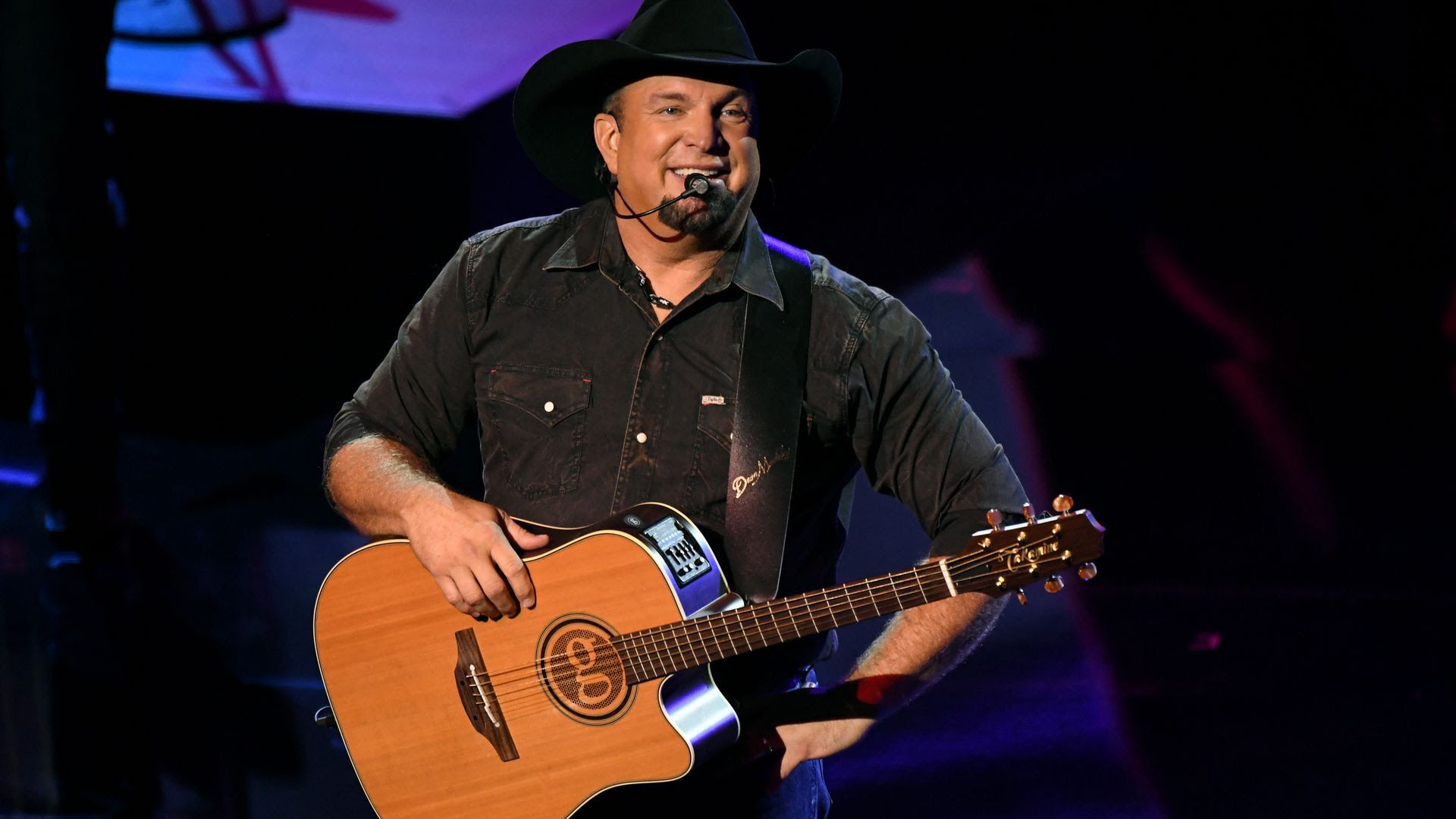 Garth Brooks holding a guitar and laughing with the audience.