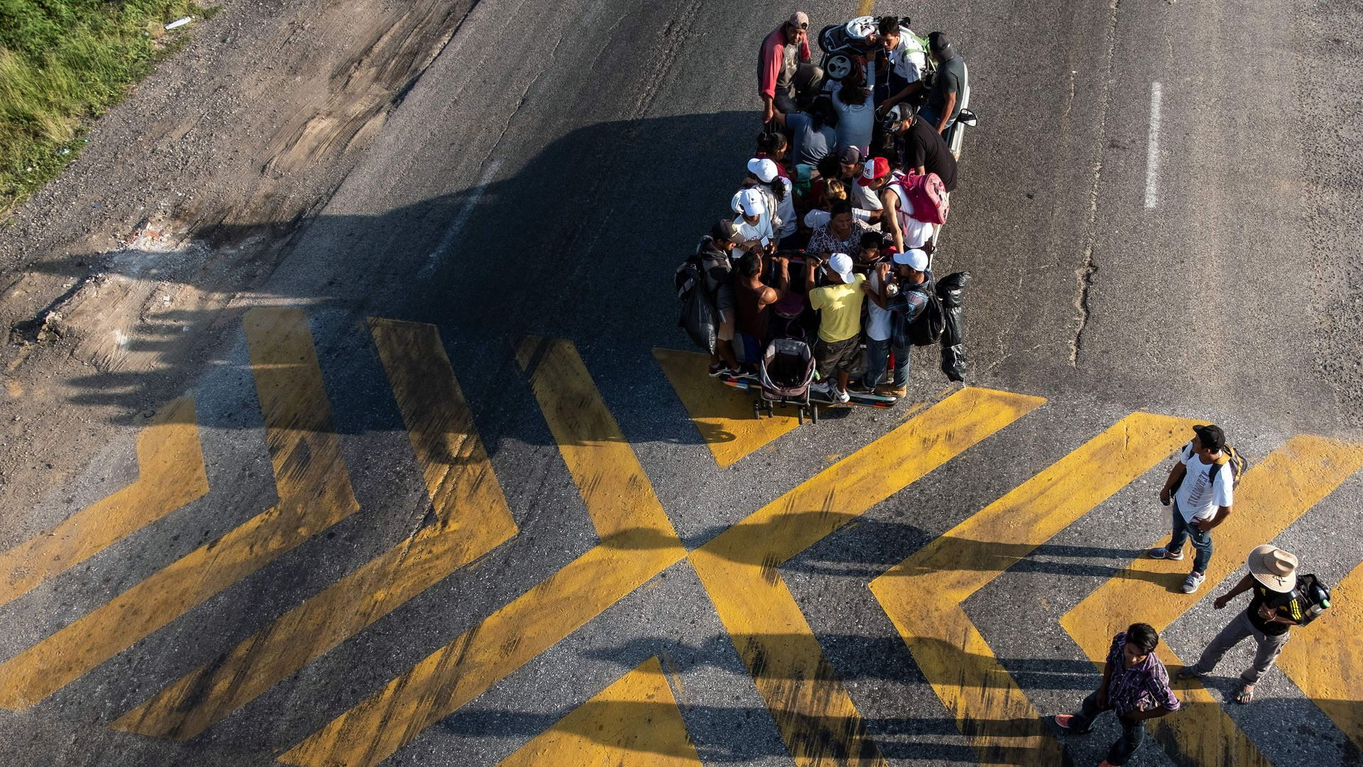 An aerial shot of a truck on a road with Central American migrants who are members of the caravan sitting on top of it