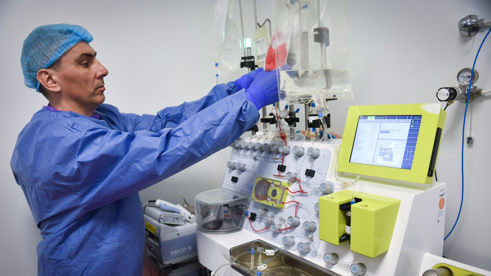 A lab tech handles a CliniMACS Prodigy automated device used for cell processing