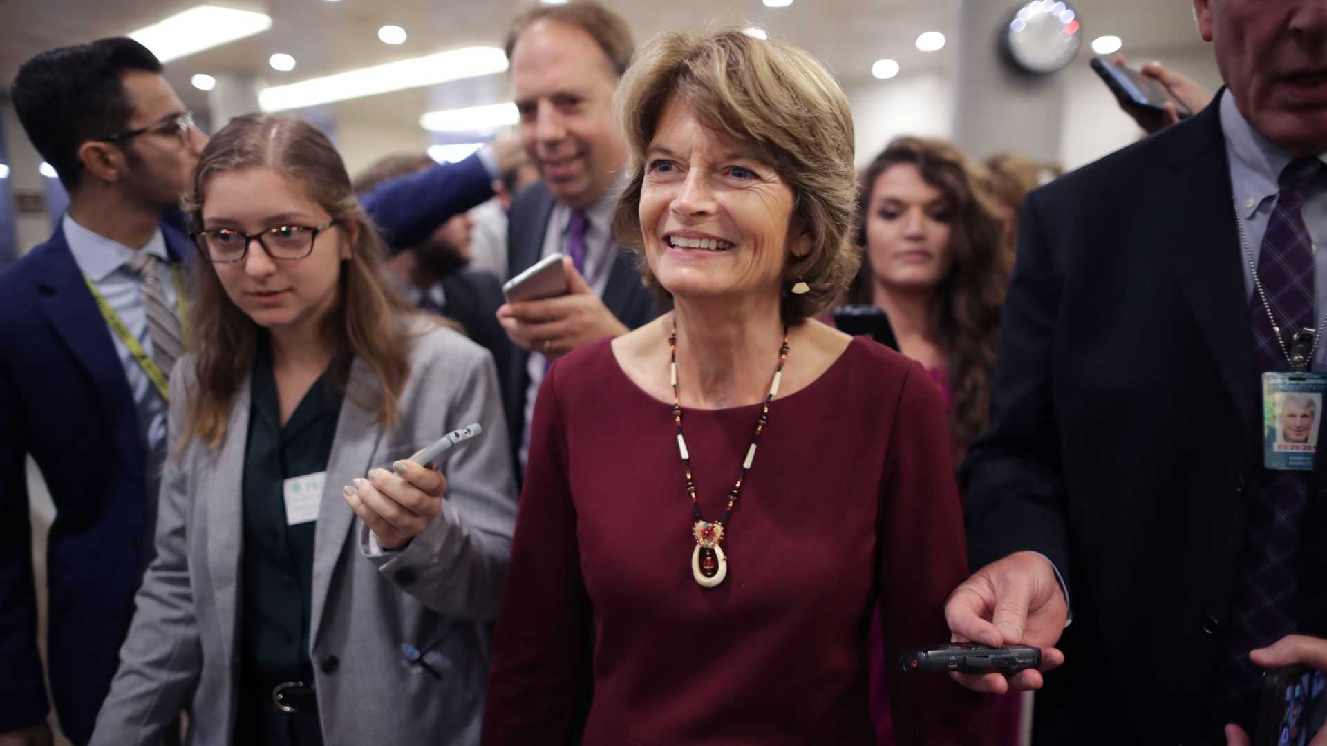 Lisa Murkowski smiling in the Capitol Hill basement surrounded by reporters.