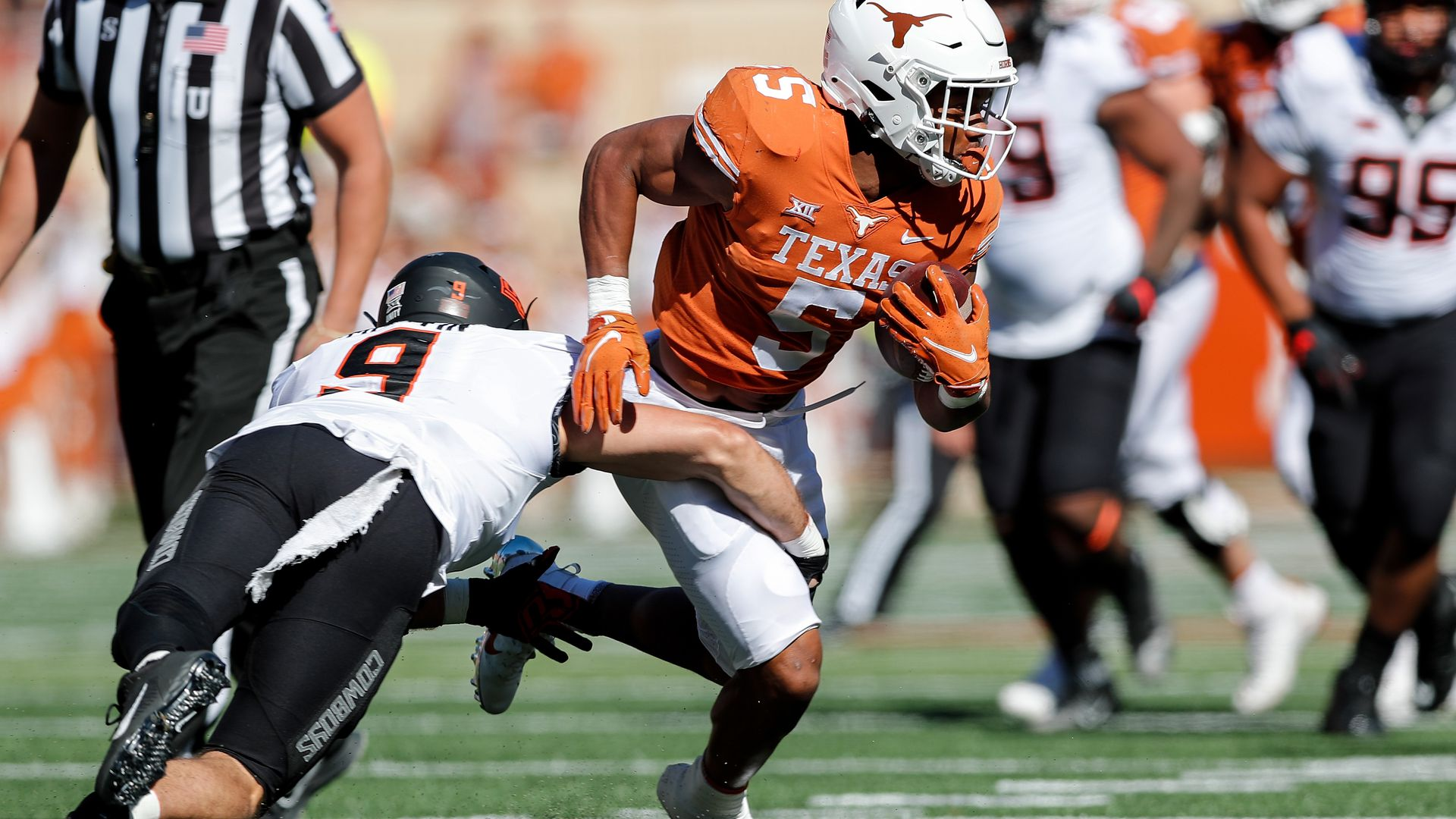 Bijan Robinson of the University of Texas attempts to elude a would-be Oklahoma State tackler.