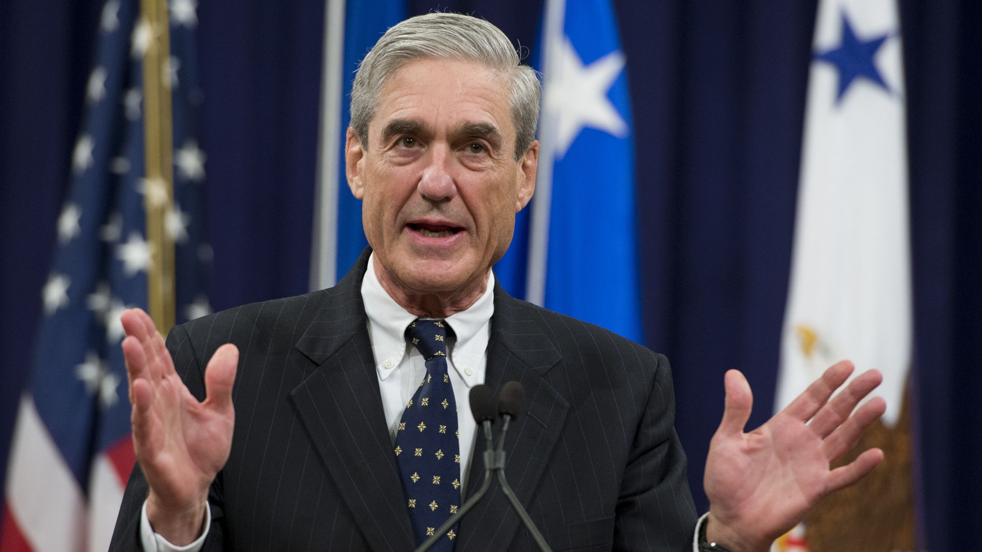 Bob Mueller gestures while speaking with his hands up.