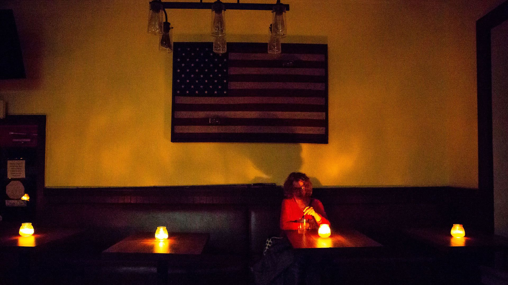 A woman sitting in a restaurant without electricity