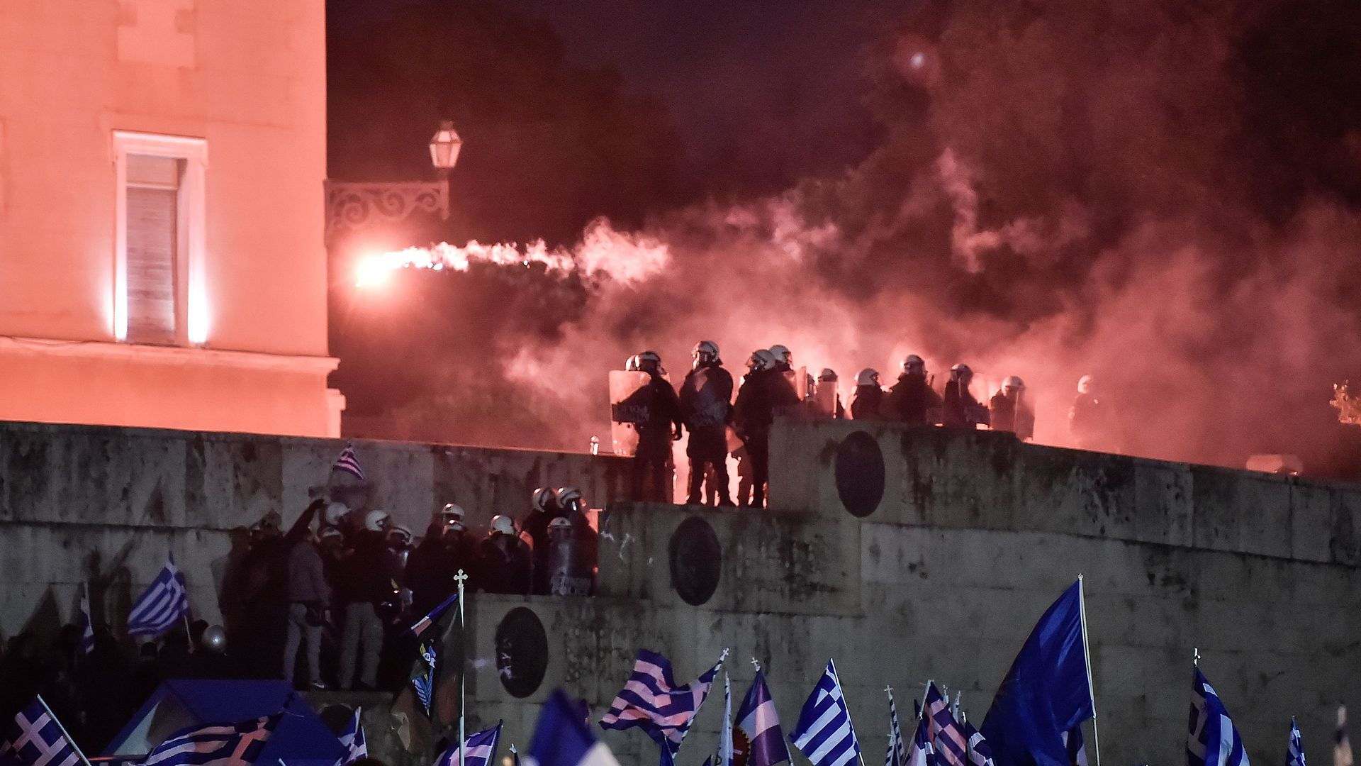 Protesters with Greek flags throw flares near riot police outside Greek Parliament.