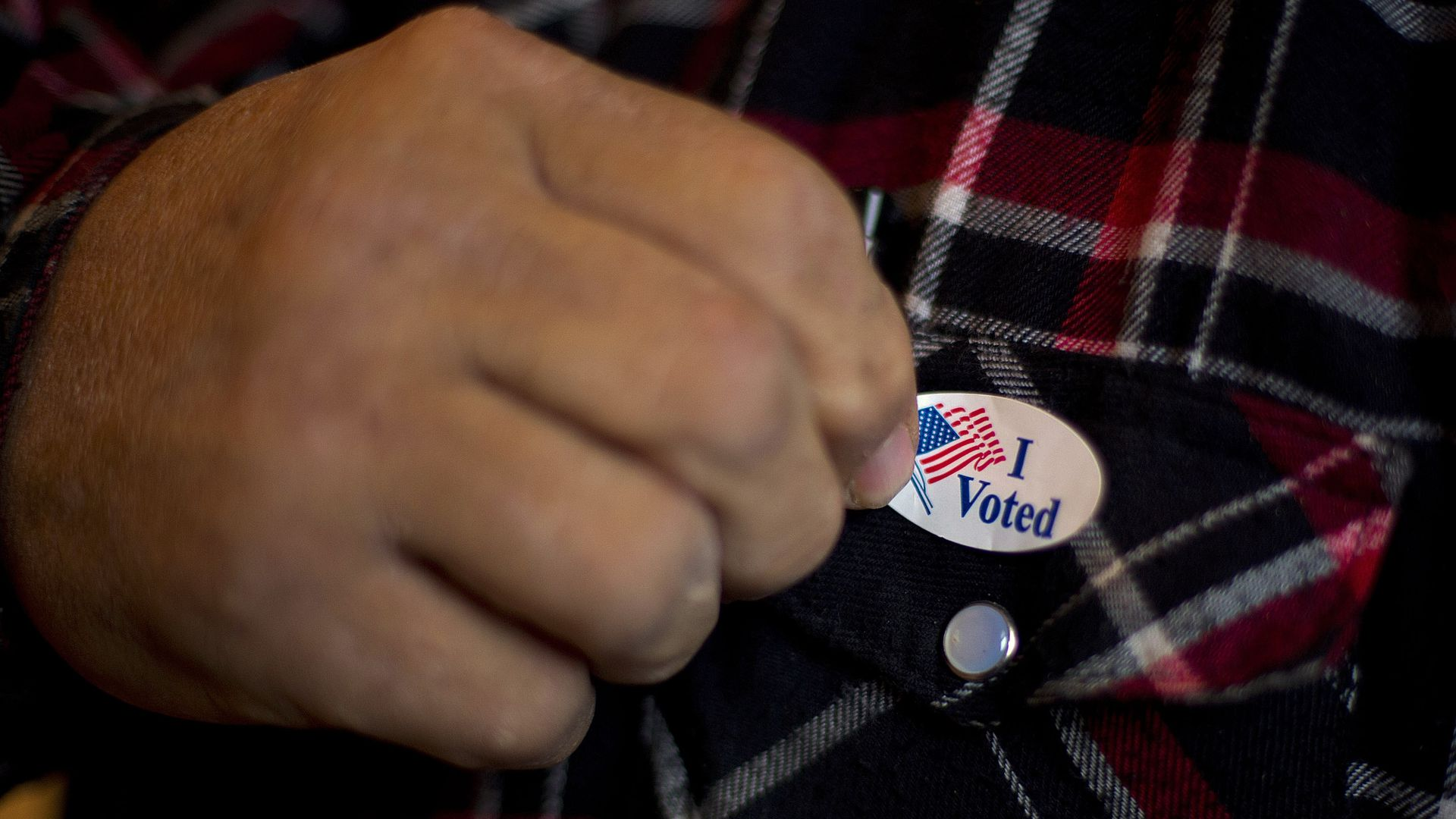 "Man affixes an ""I voted"" sticker."