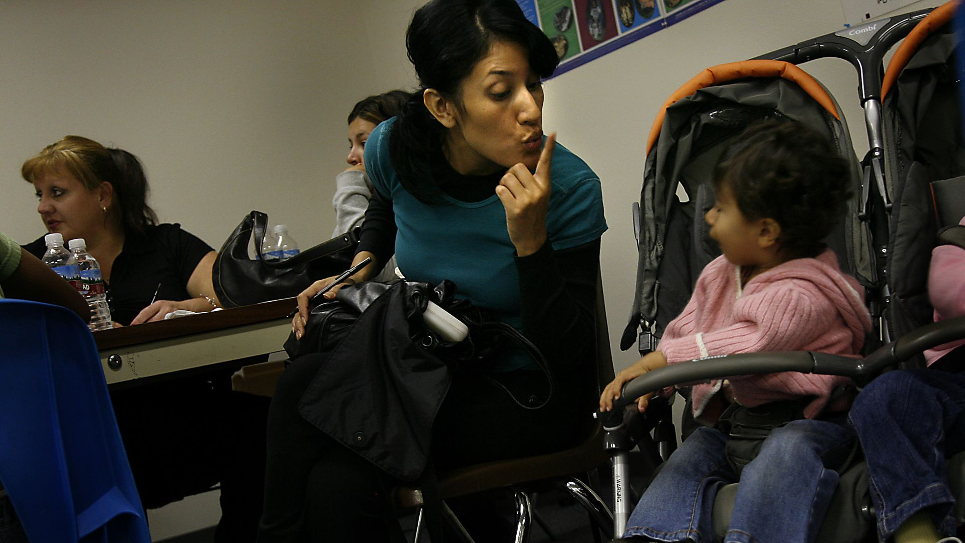 Delia Garcia, of Tustin, tries to quiet her daughter Nicole, 1, while she attempts to fill out paperwork