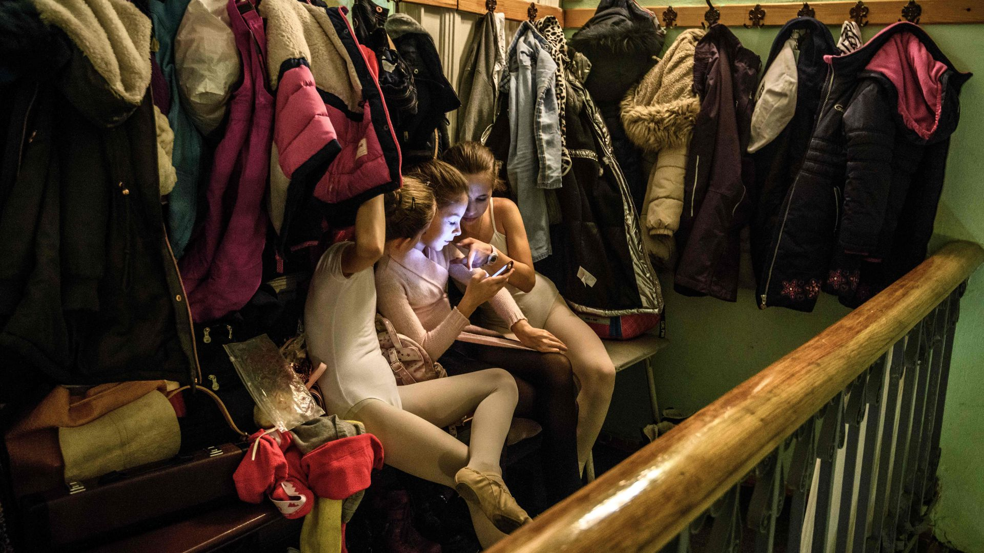Young girls use a smartphone in a coat room.