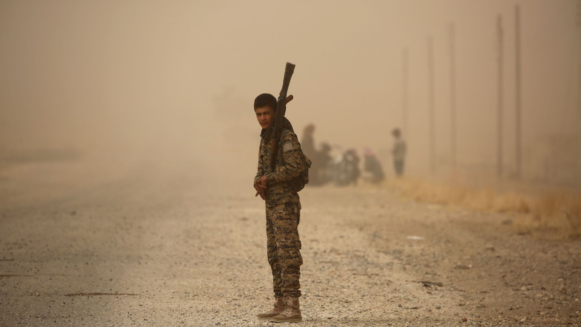 A member of the Syrian Democratic Forces stands with a weapon in a sandstorm.