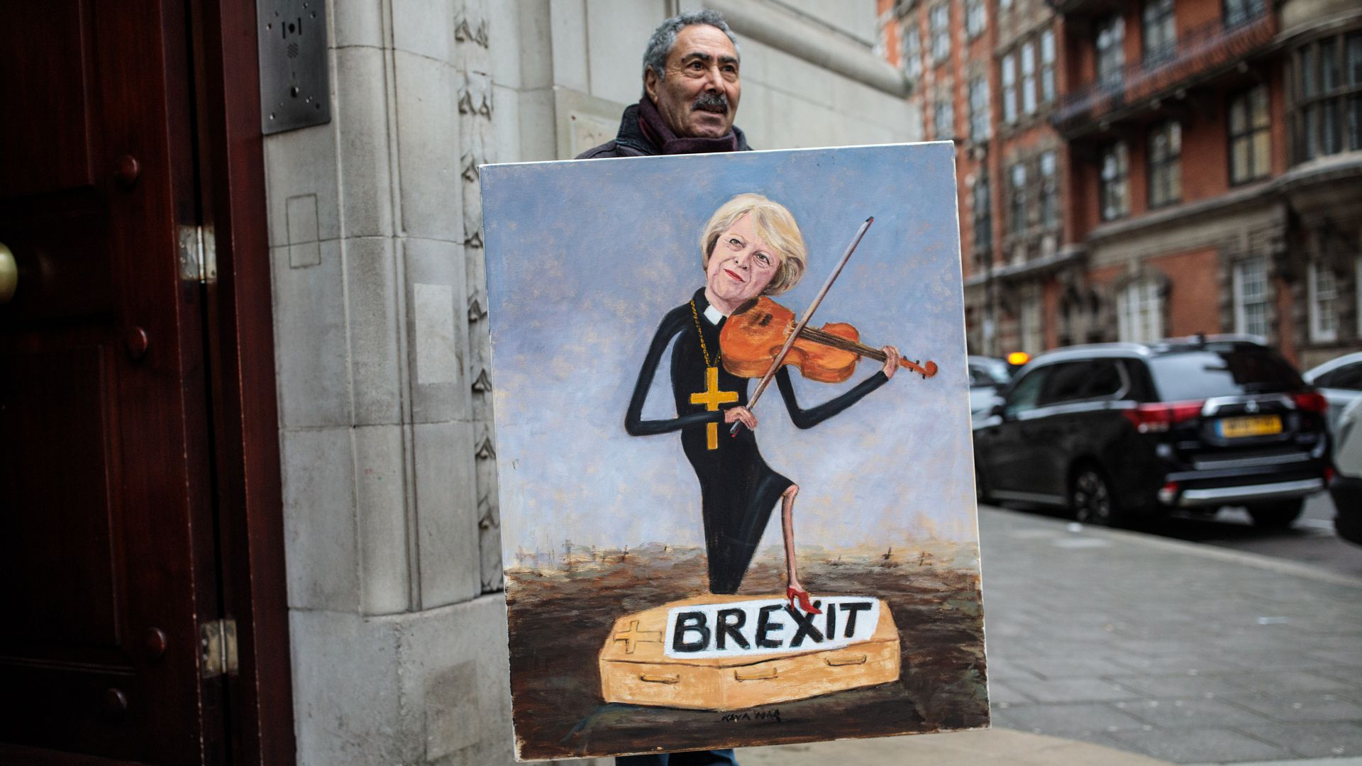 Political artist Kaya Mar stands with his painting depicting Prime Minister Theresa May playing a violin outside Millbank Studios in Westminster on January 16, 2019 in London, England.