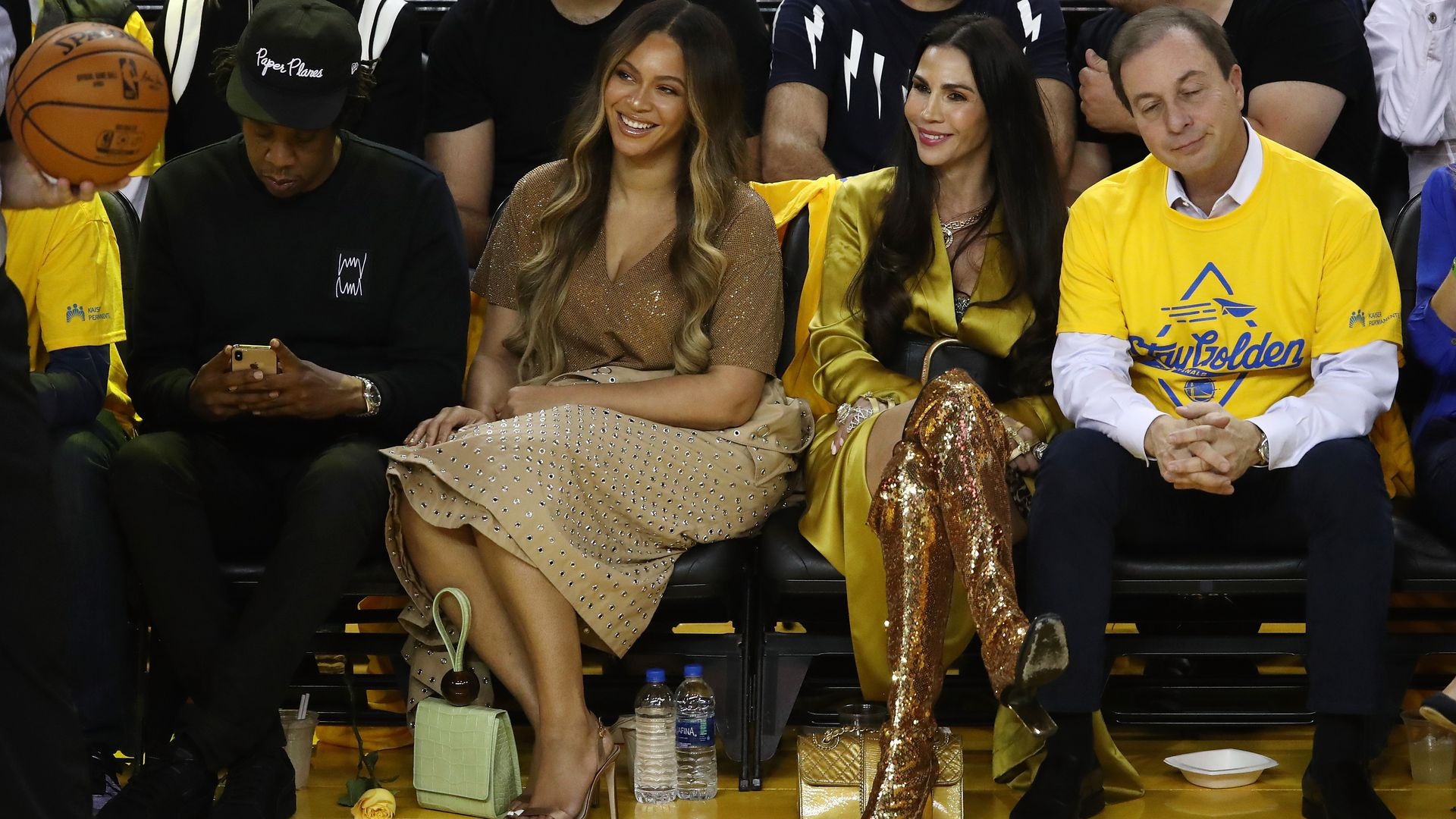 In this image, Beyonce sits next to others on a courtside basketball game.