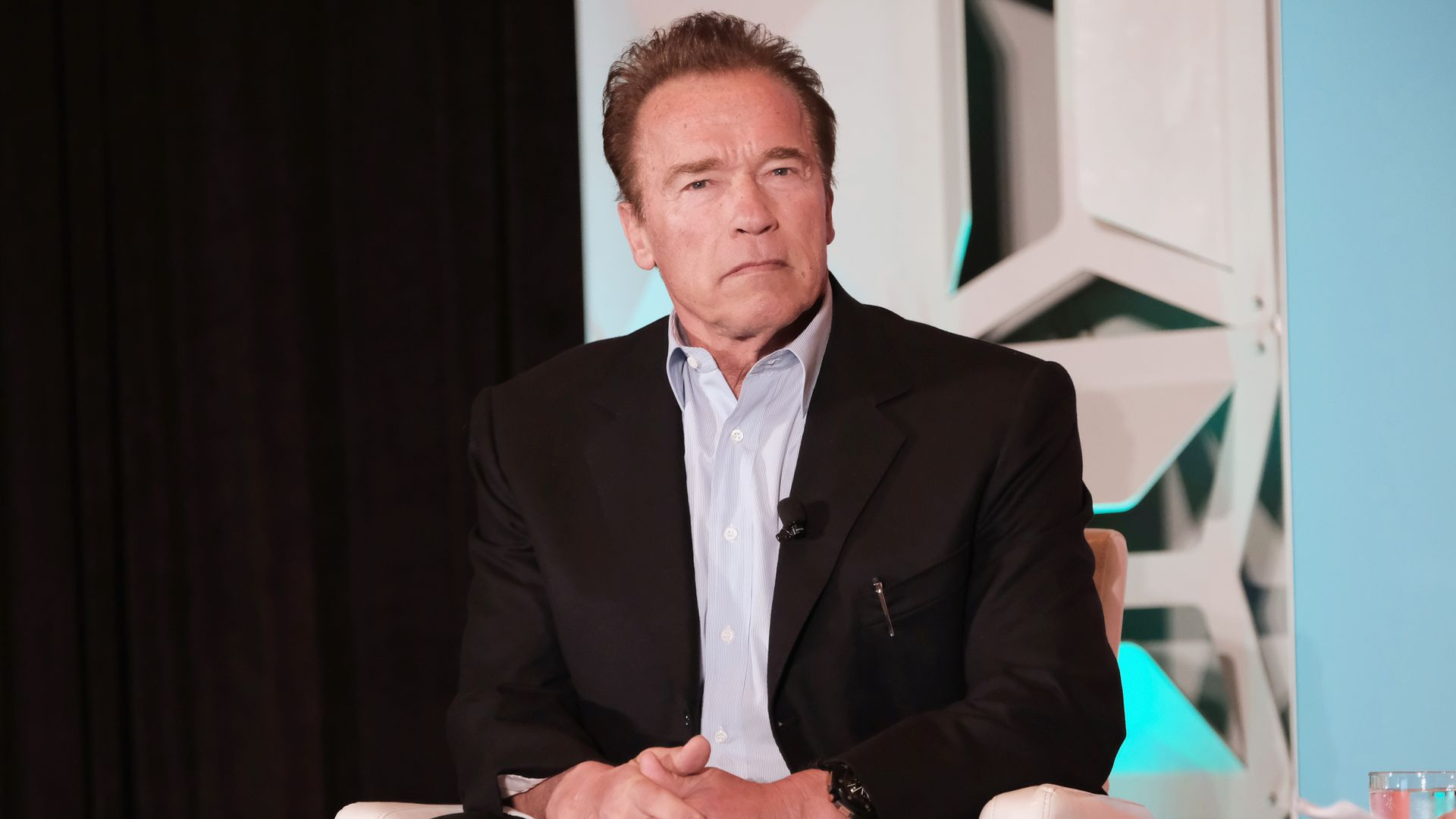 Arnold Schwarzenegger sitting down in a while chair with a serious expression