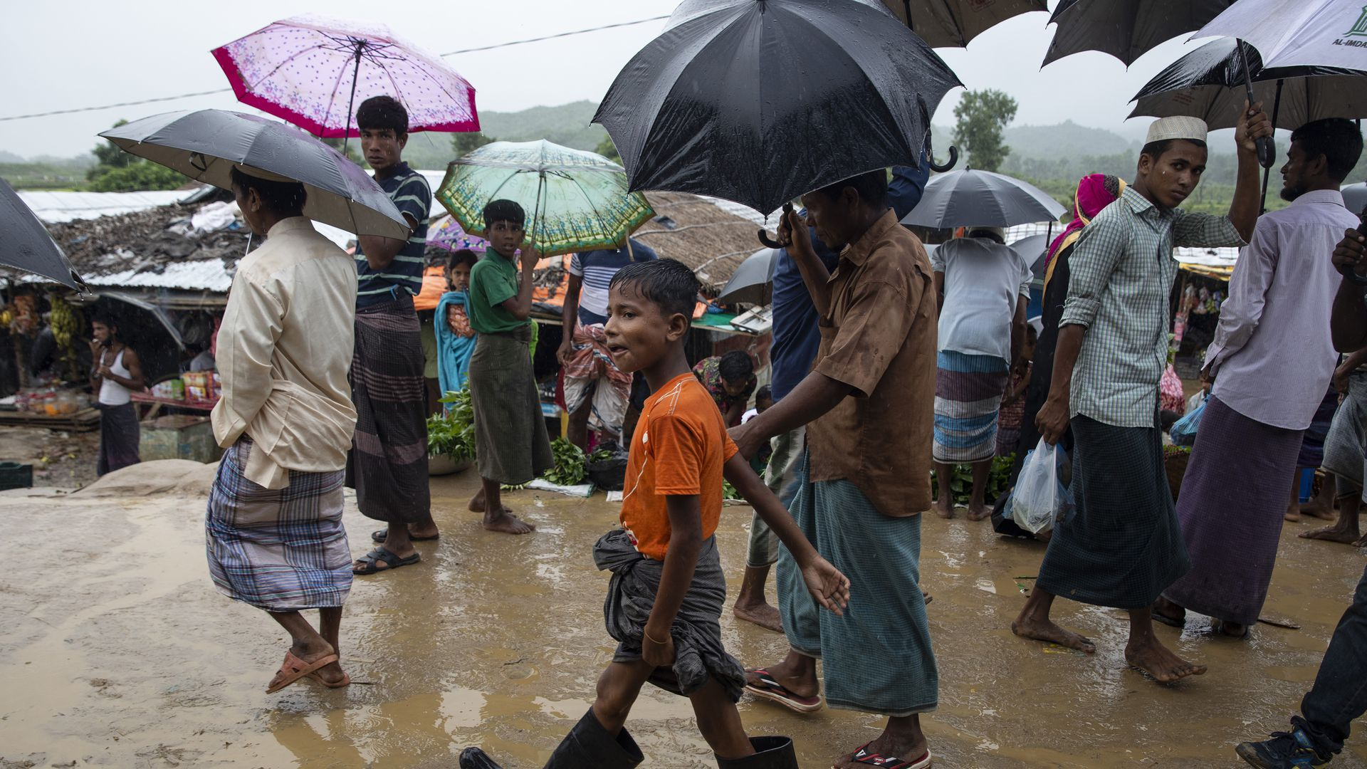 Monsoon rains hit the refugee camps as Rohingya walk through a local market August 28, 2018 in Unchiprang refugee camp, Cox's Bazar, Bangladesh.