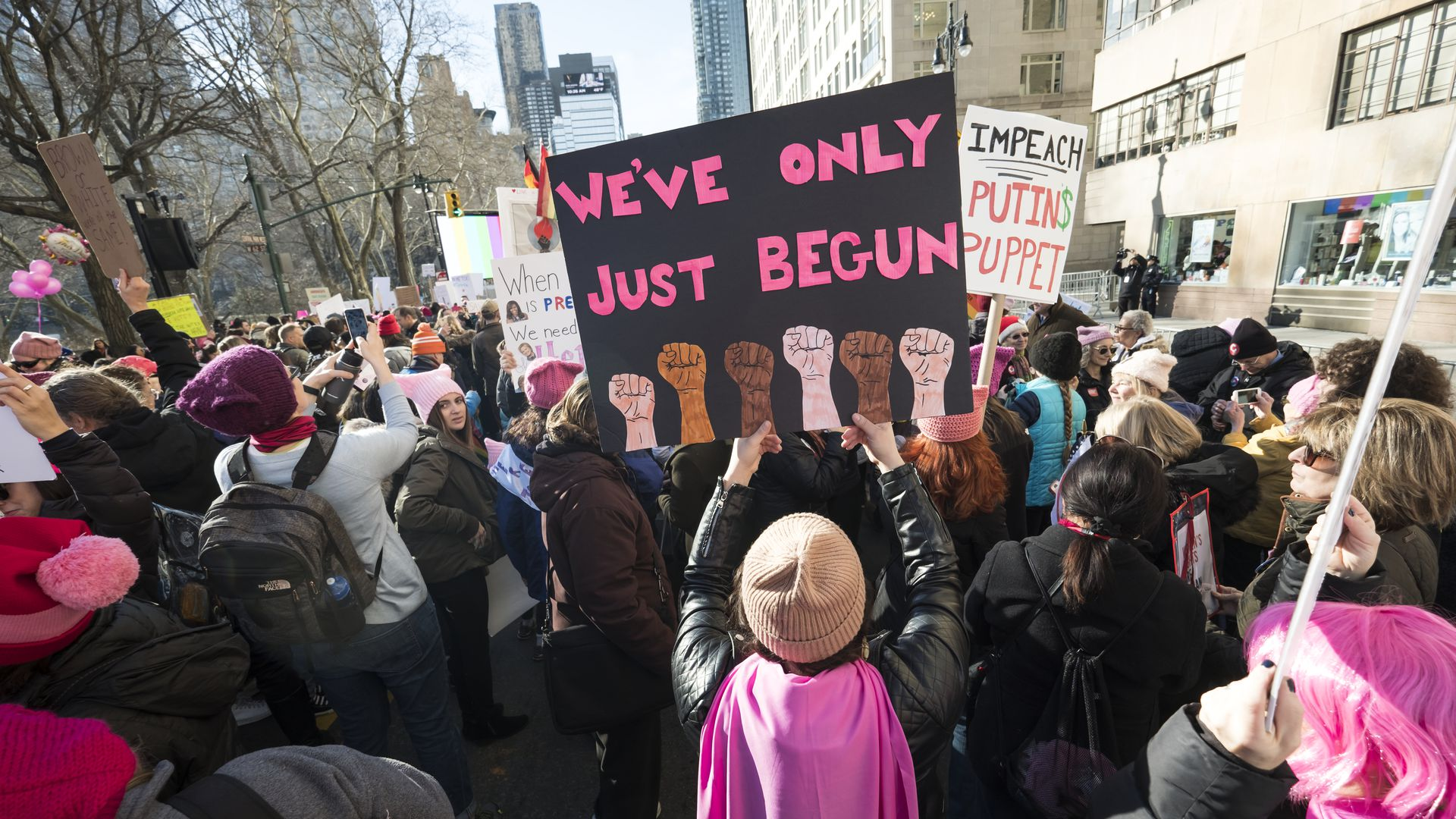 "Women's March 2018; A protestor holds a sign that reads, ""We've only just begun."""