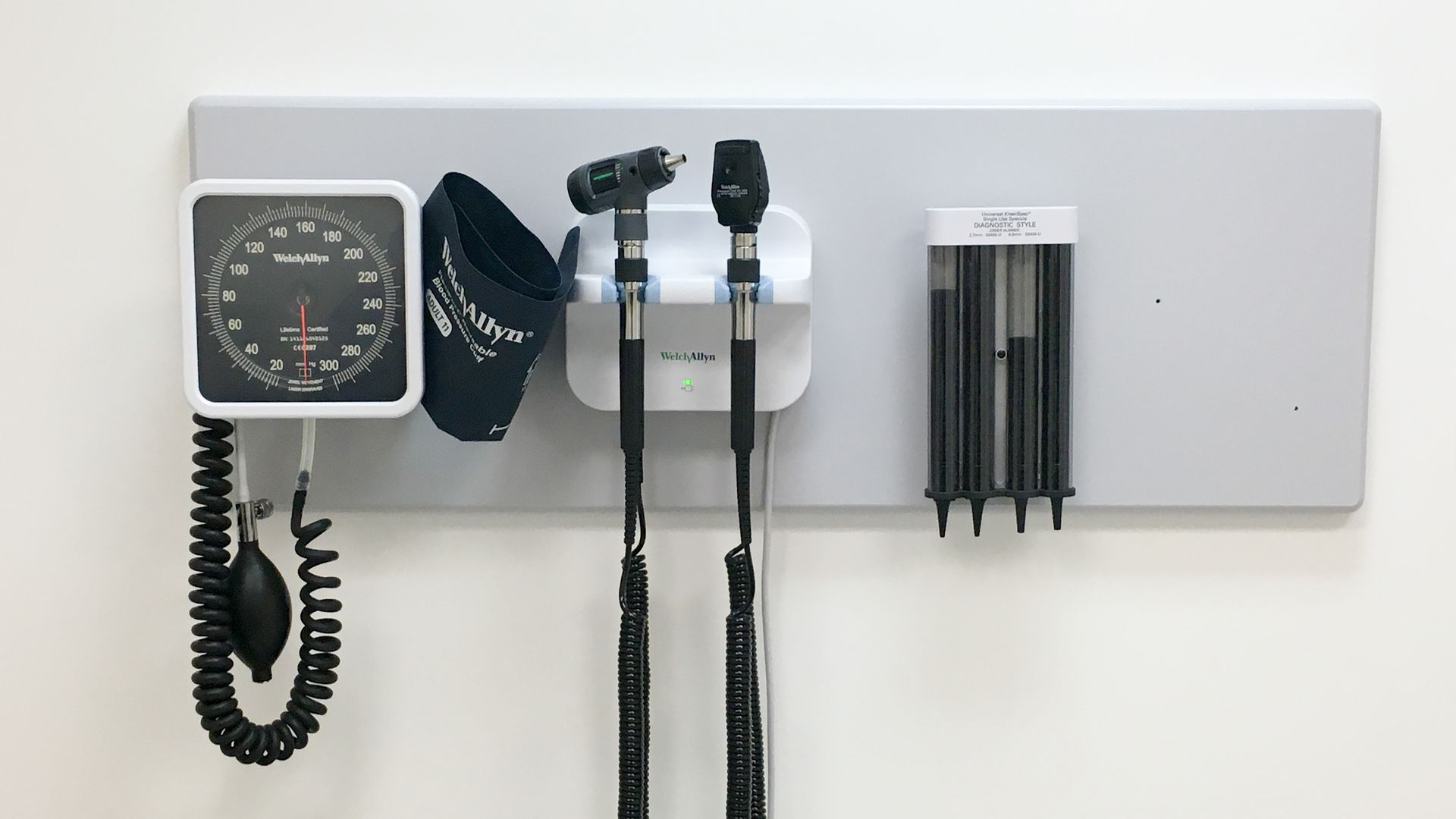 Tools on the wall of a doctor's office, including monitor to measure blood pressure