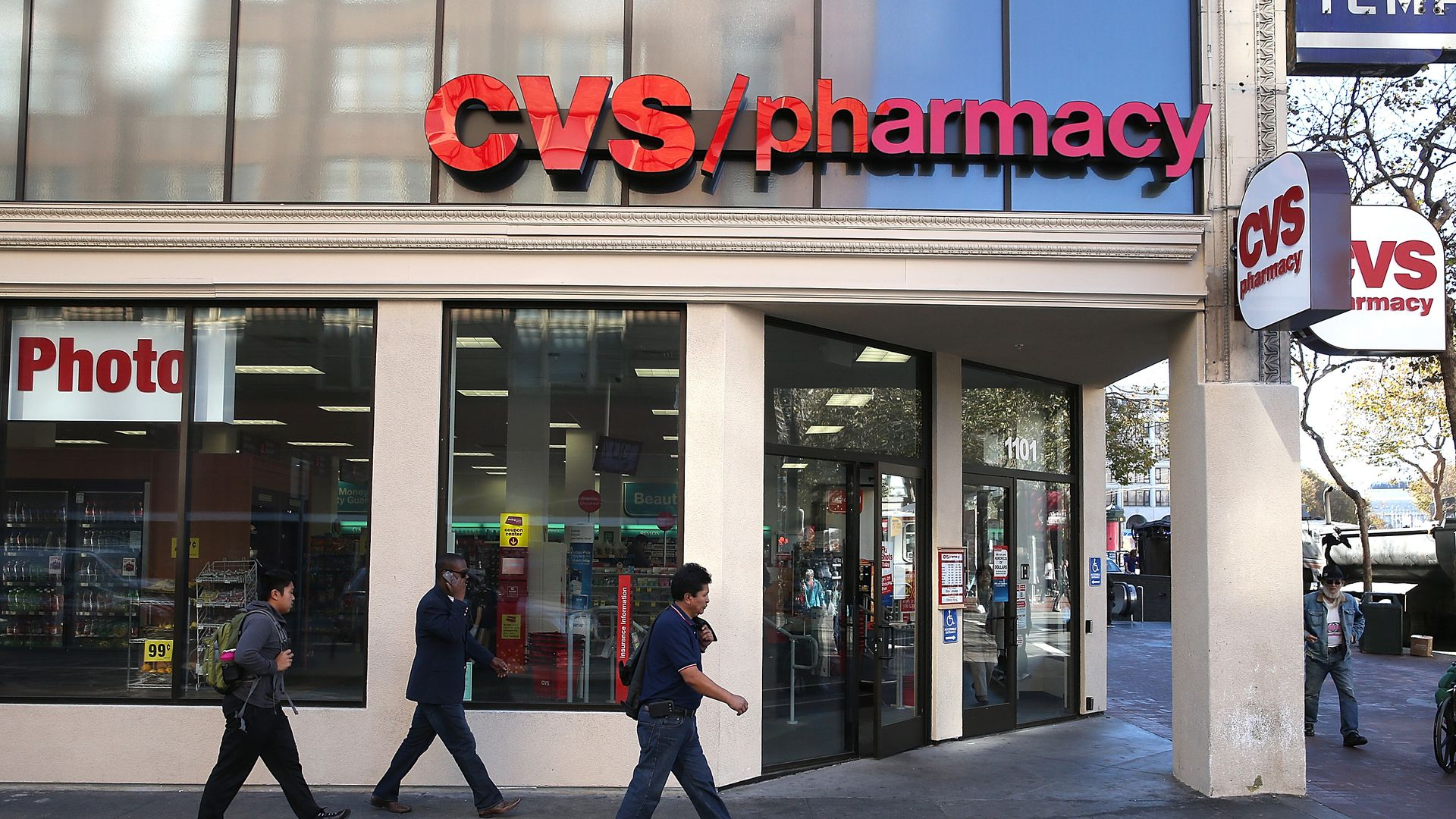 People walk outside a CVS pharmacy store.