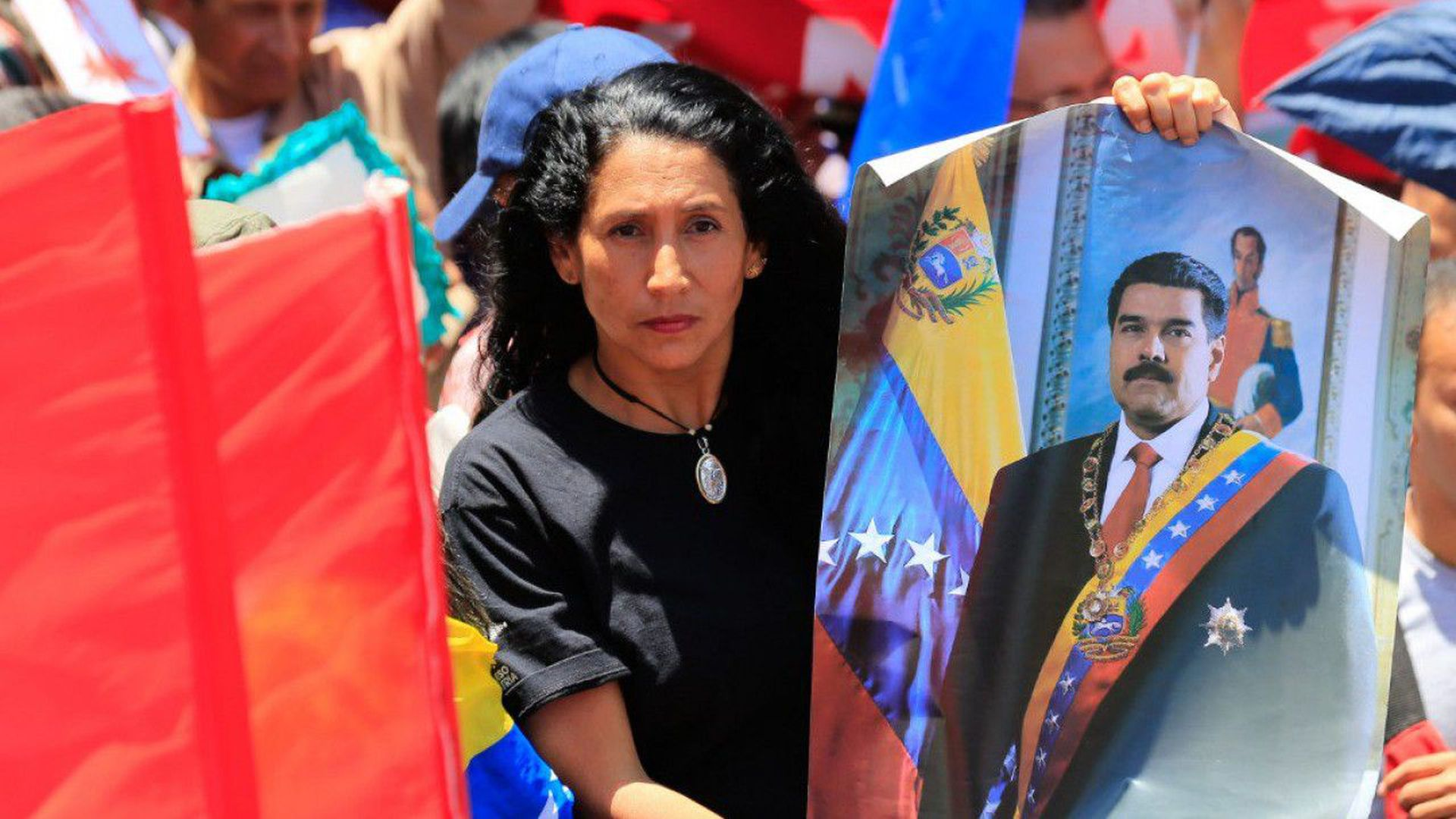 In this image, a woman holds a poster of Maduro outside during a protest.