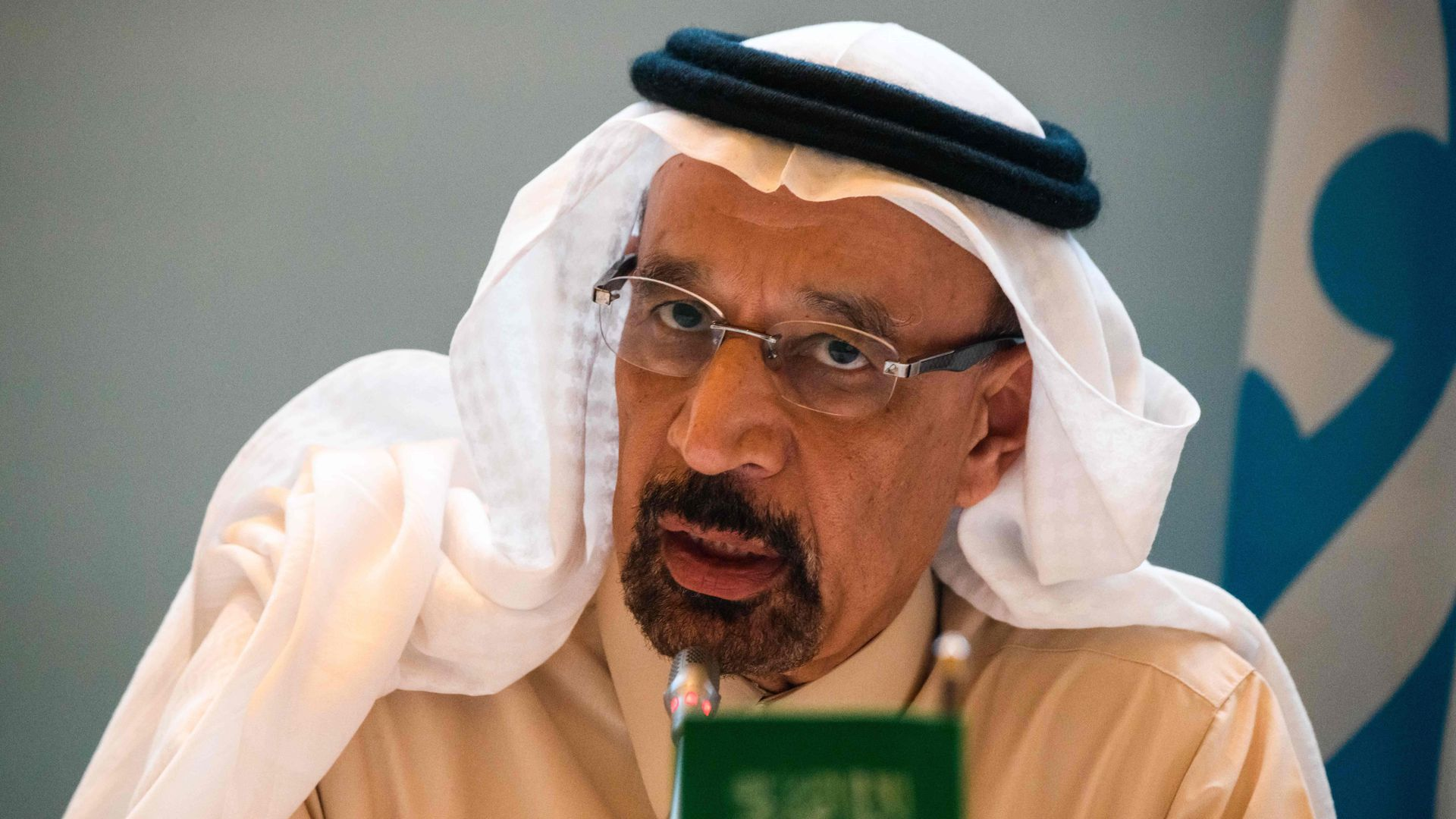 This image is a close-up of Saudi Energy Minister Khalid Al Falih talking. A blurred miniature Saudi Arabian flag sits in front of him.