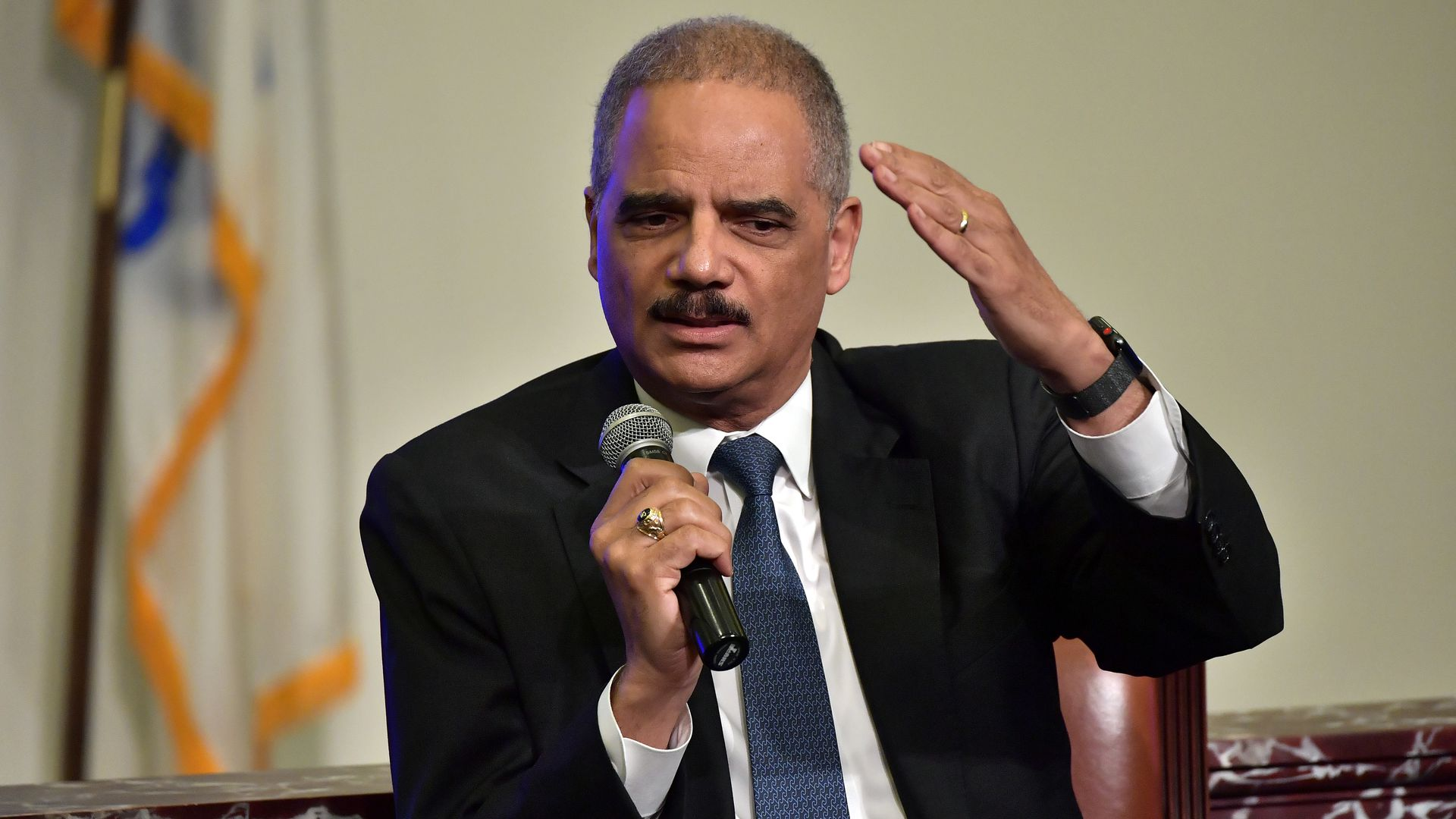 Eric Holder gestures with one arm.