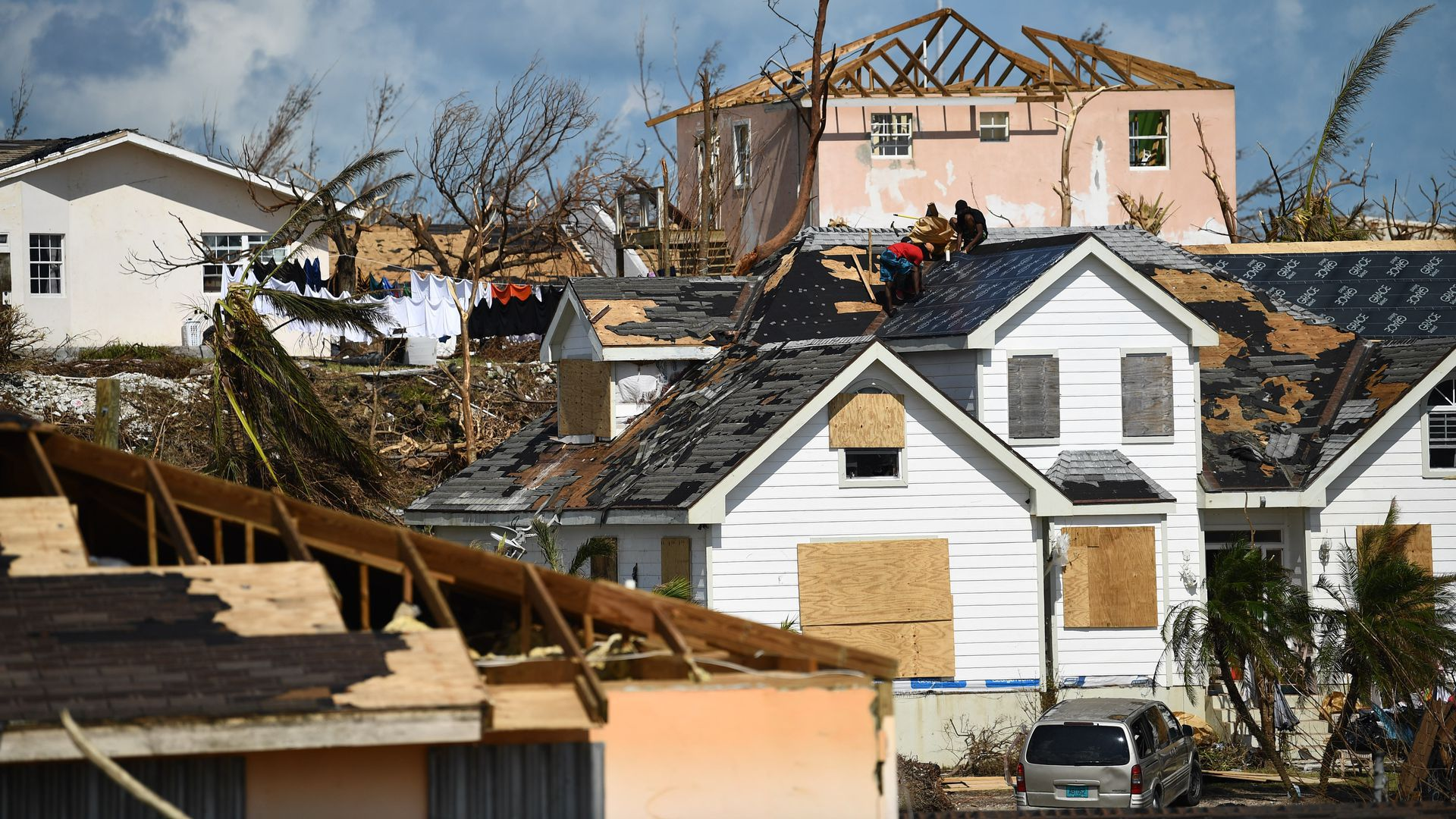 """Residents work on a roof in the """"Mudd"""" neighborhood of Marsh Harbour, Great Abaco."""