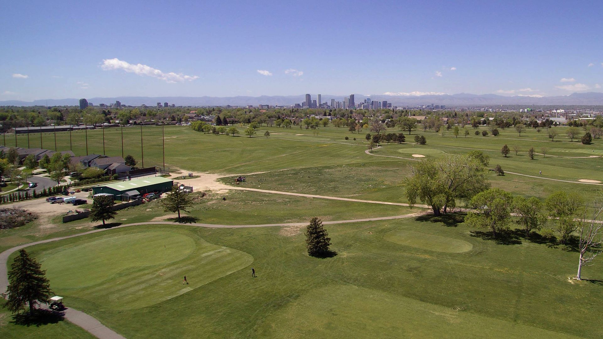 A photo of the sprawling Park Hill Golf Course with the Denver skyline in the backdrop