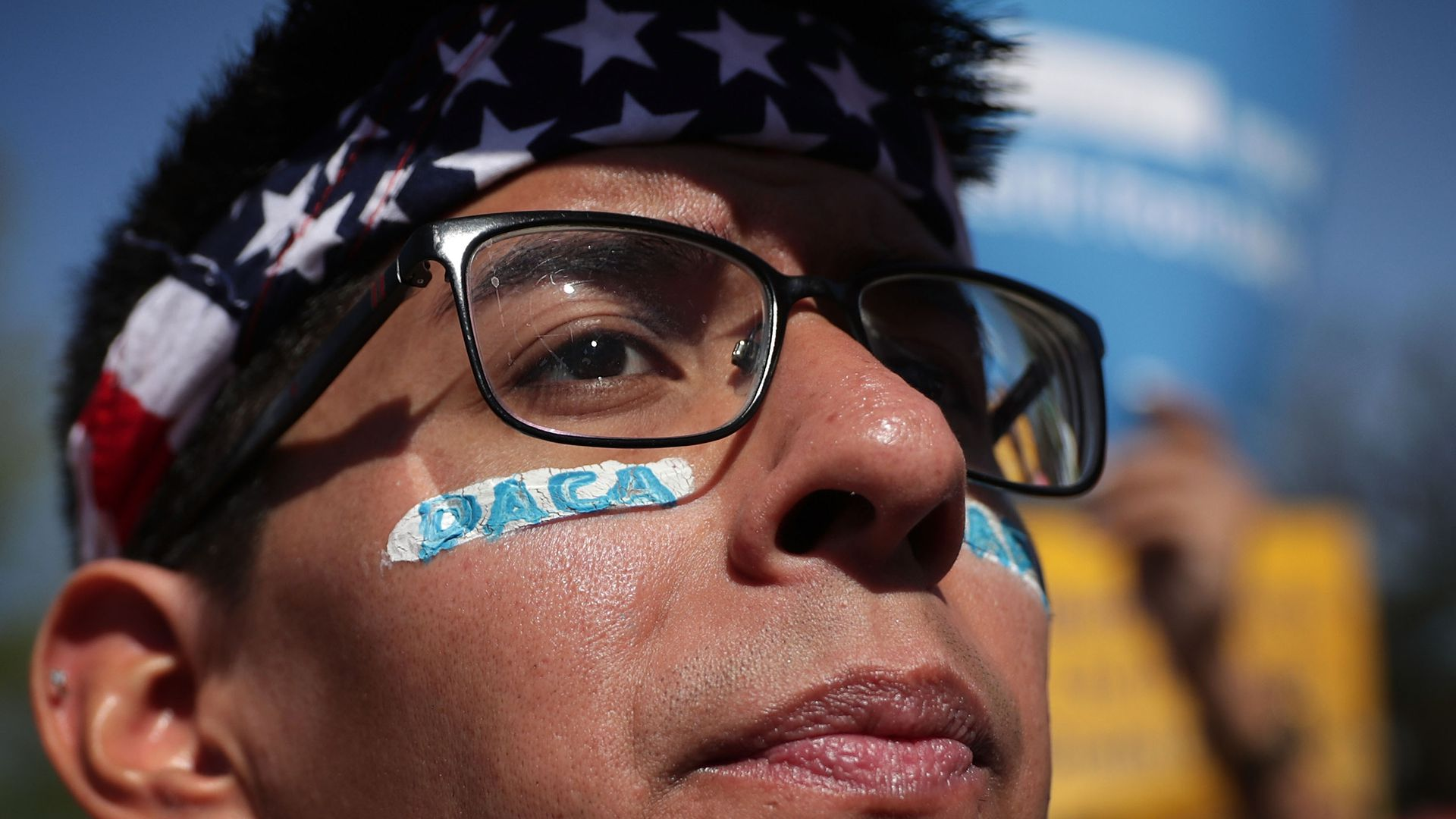 "DACA protestor with glasses, American flag bandana and stickers under his eyes with ""DACA"" written on them"