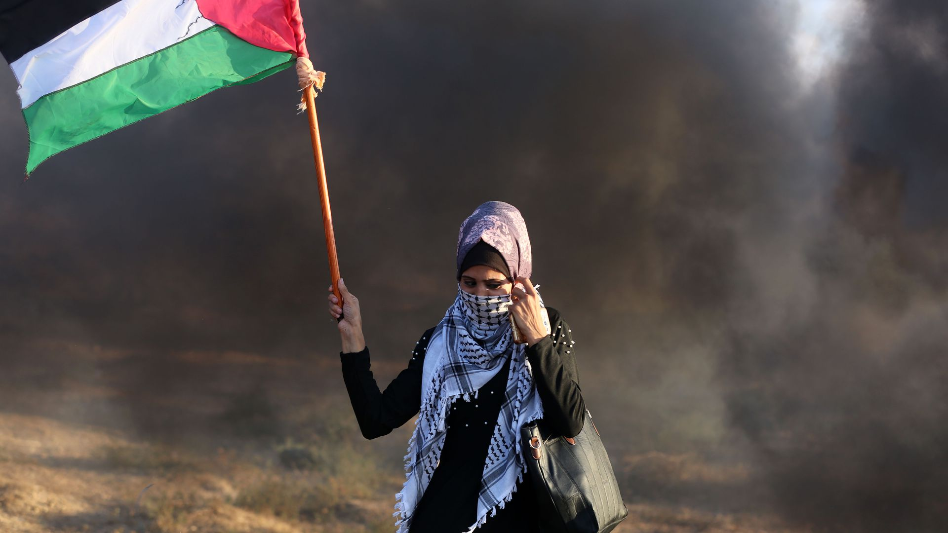 A woman holding a Palestinian flag, standing in black smoke.