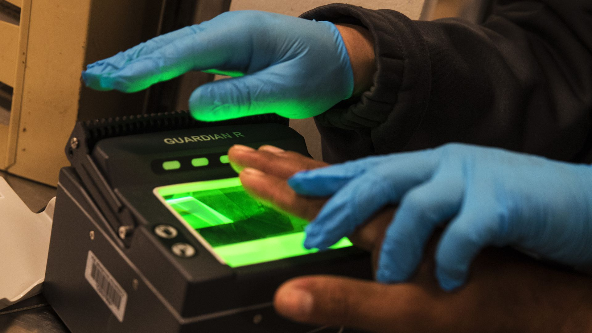 Gloved hands pressing another ungloved hand to a fingerprint scanner
