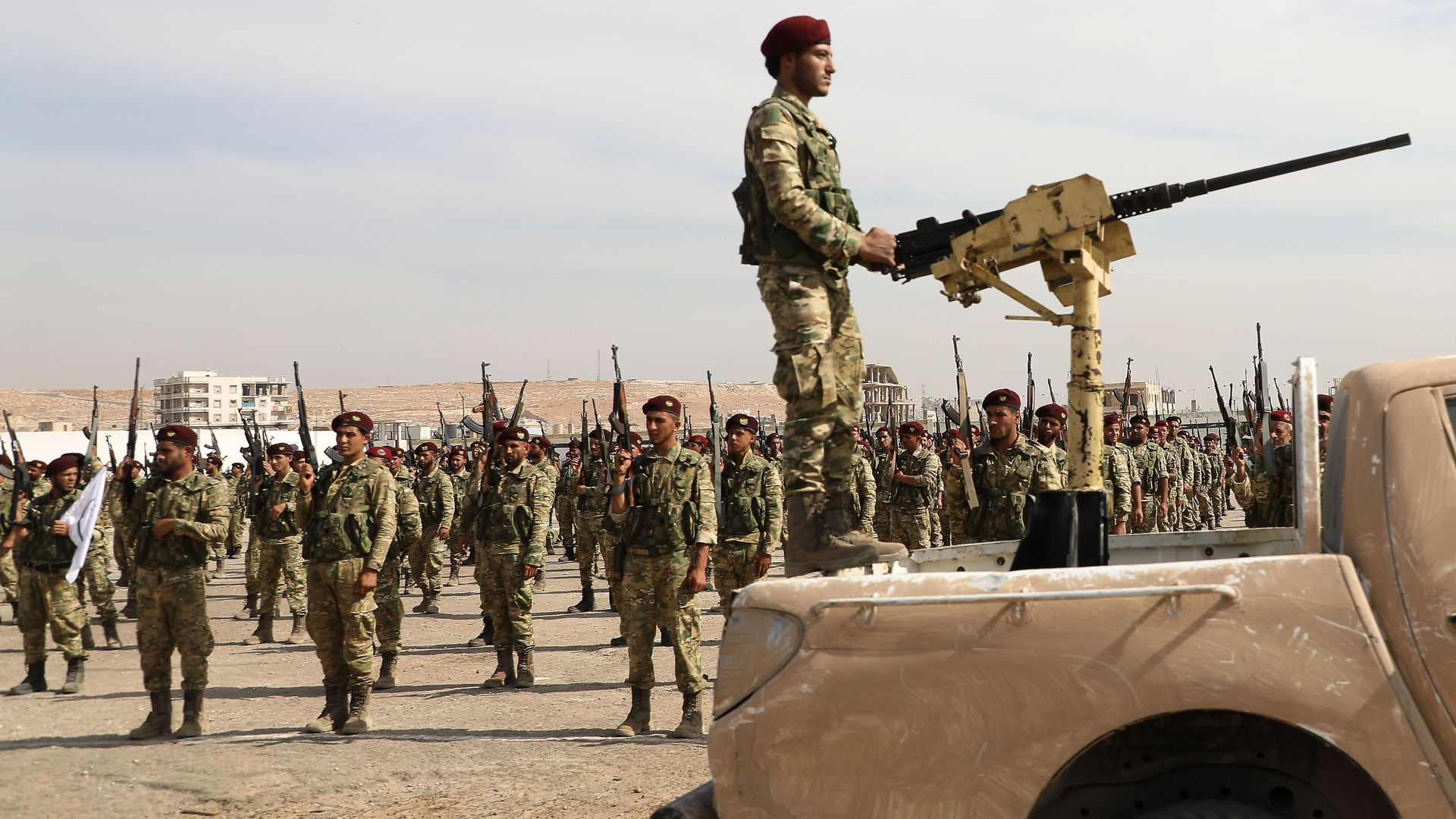 In this image, a soldier stands in the back of a truck while holding onto a stationary machine gun while rows of soldiers stand behind him