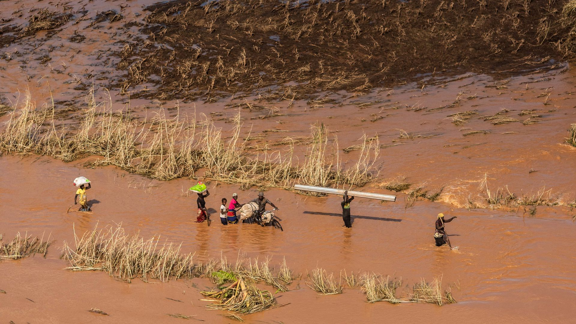 people wading through floodwaters in Mozambique