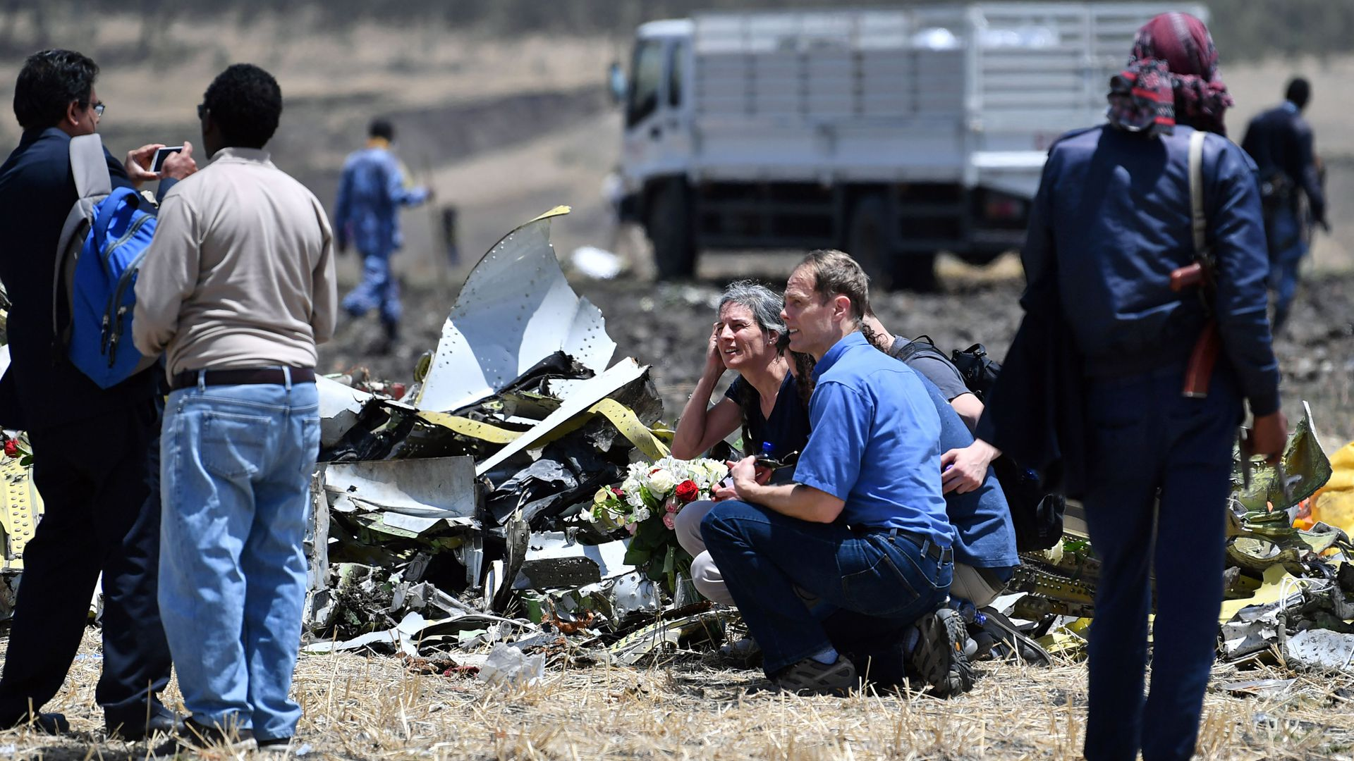 Relatives of the victims of the Ethiopian plane crash sit in a field among debris, looking concerned.