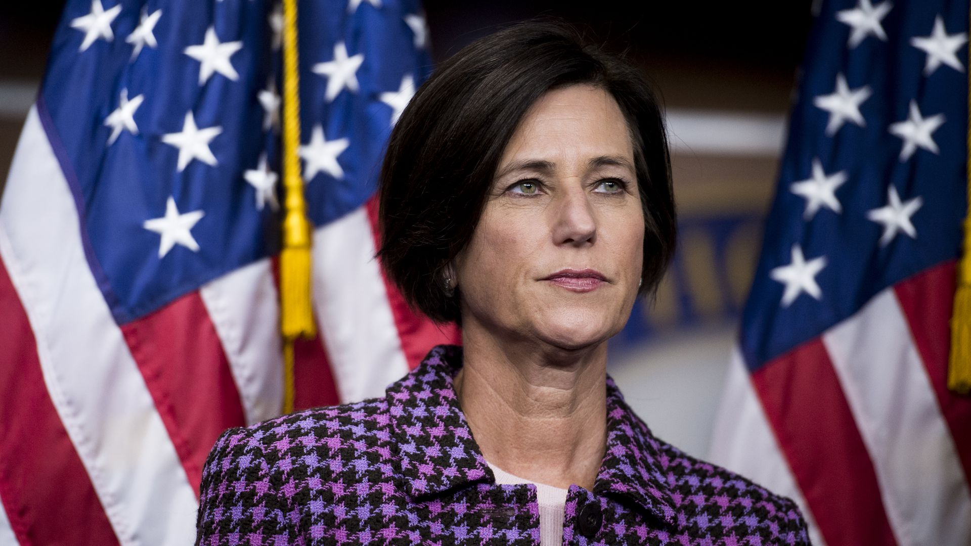 Mimi Walters in a purple plaid jacket standing in front of two American flags