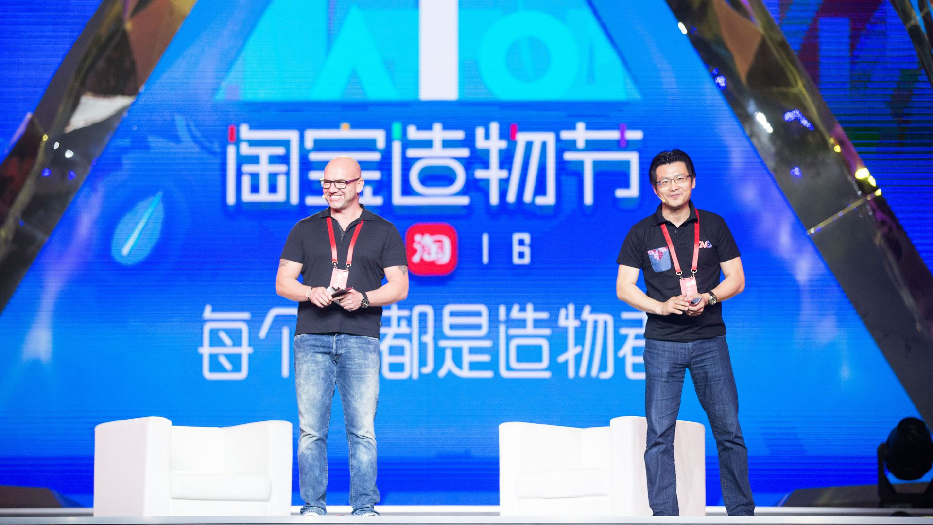 Two men in back T-shirts and jeans stand on a stage with two white chairs.
