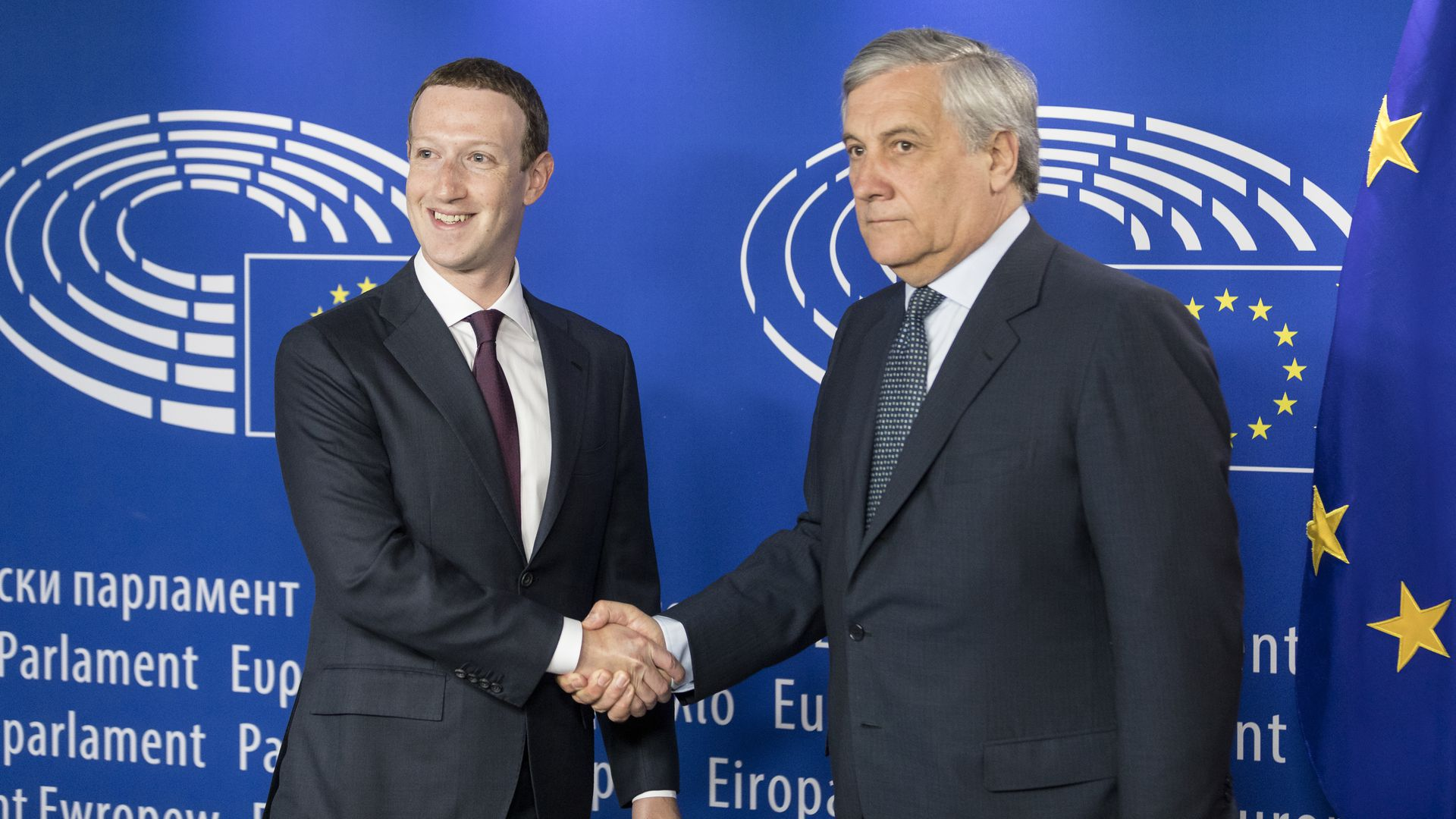 Mark Zuckerberg, smiling, shakes the hand of an unsmiling lawmaker in the EU