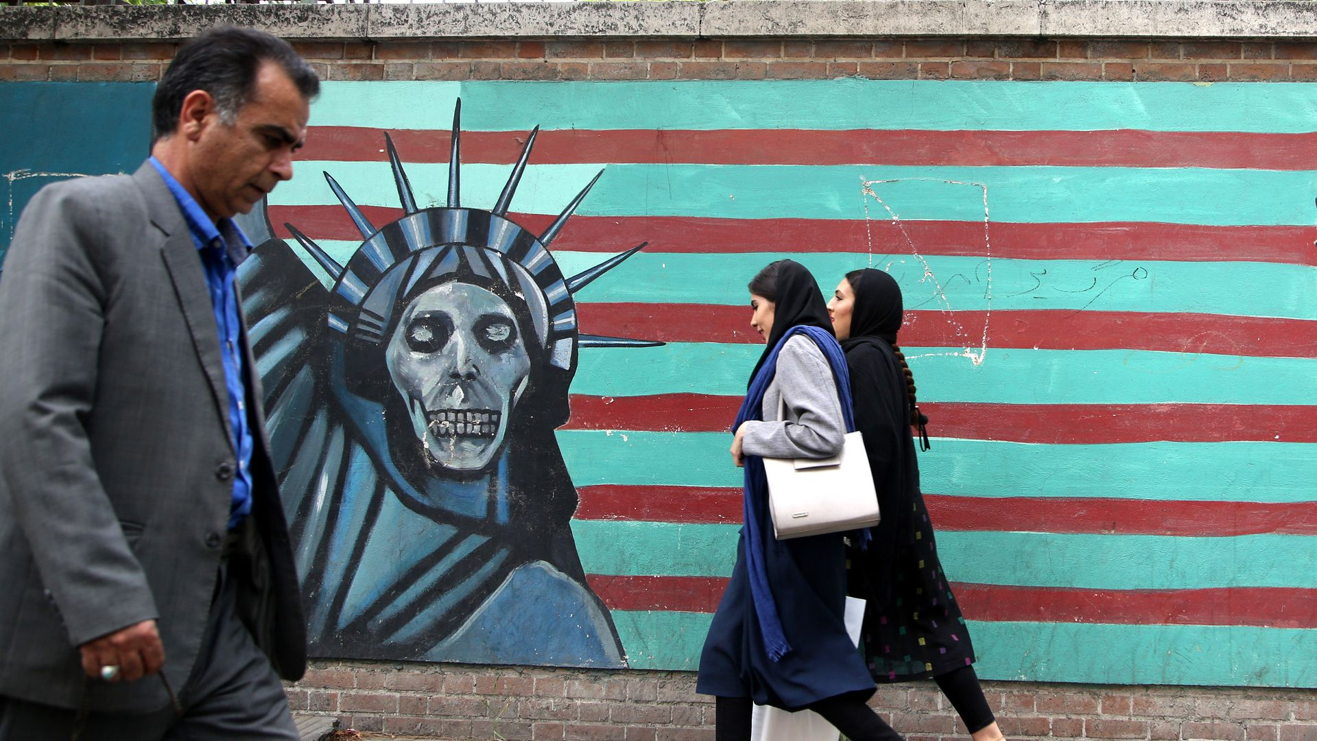 People past a mural painted on the wall of the former U.S. Embassy in Tehran, Iran, on May 9, 2018. US President Donald Trump announced 'withdrawal' from Iran nuclear deal on May 9, 2018.