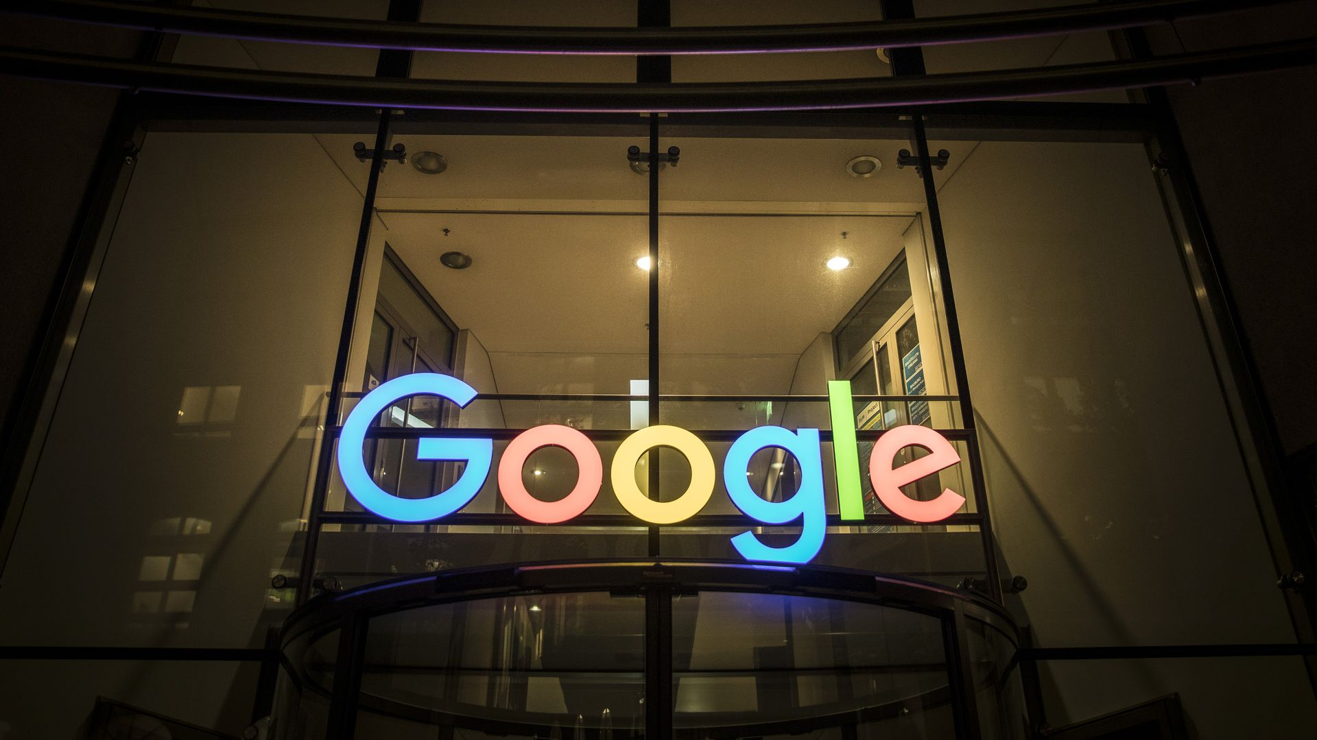 A Google sign lit up at night outside of an office