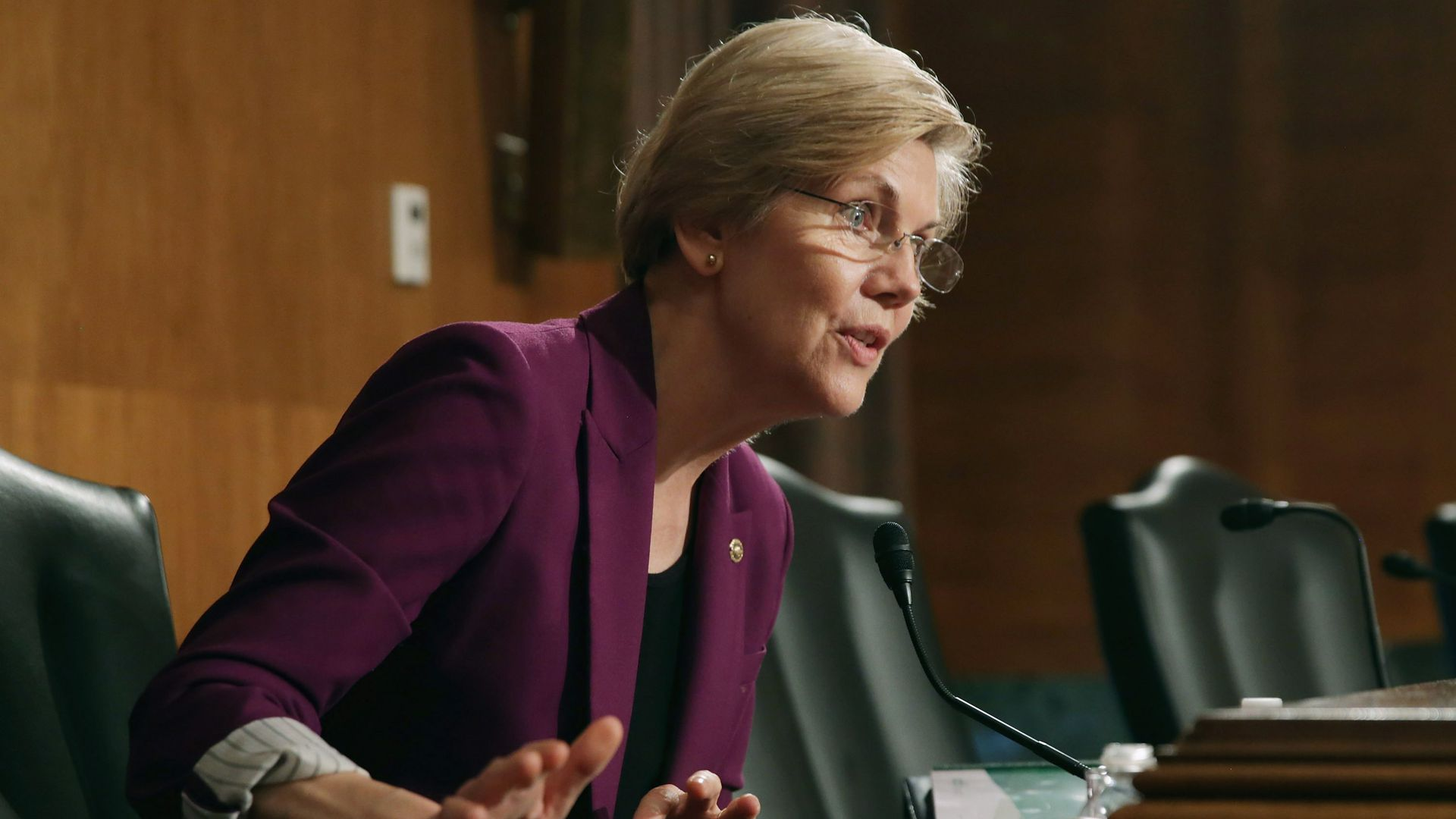 In this image, Elizabeth Warren speaks into a microphone at a committee hearing.