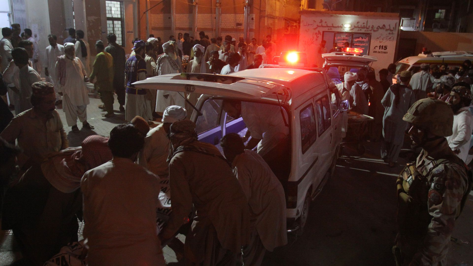 Rescue worker preparing to transport the injured and dead to a hospital after a suicide bombing in Pakistan.