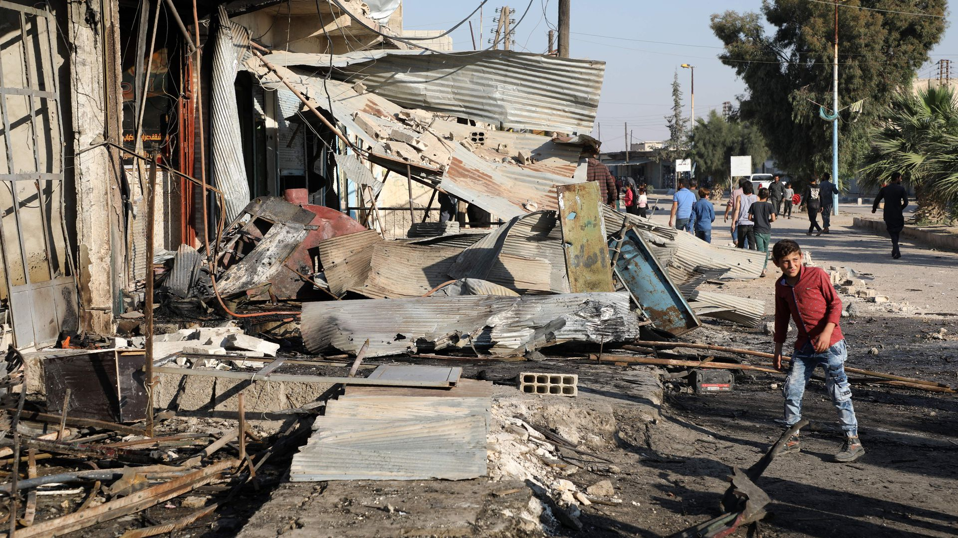 A boy man walks in front of a shop damaged in a car bomb in Syria