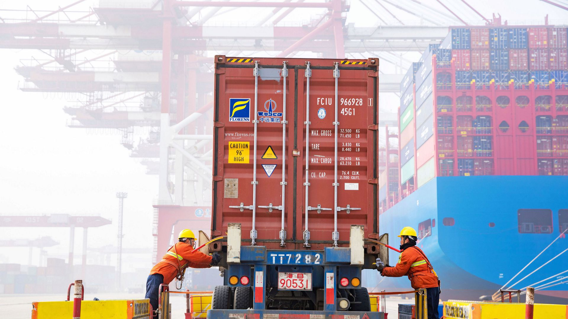 Workers check a shipping container on a truck at Qingdao Port on January 14, 2019 in Qingdao, Shandong Province of China